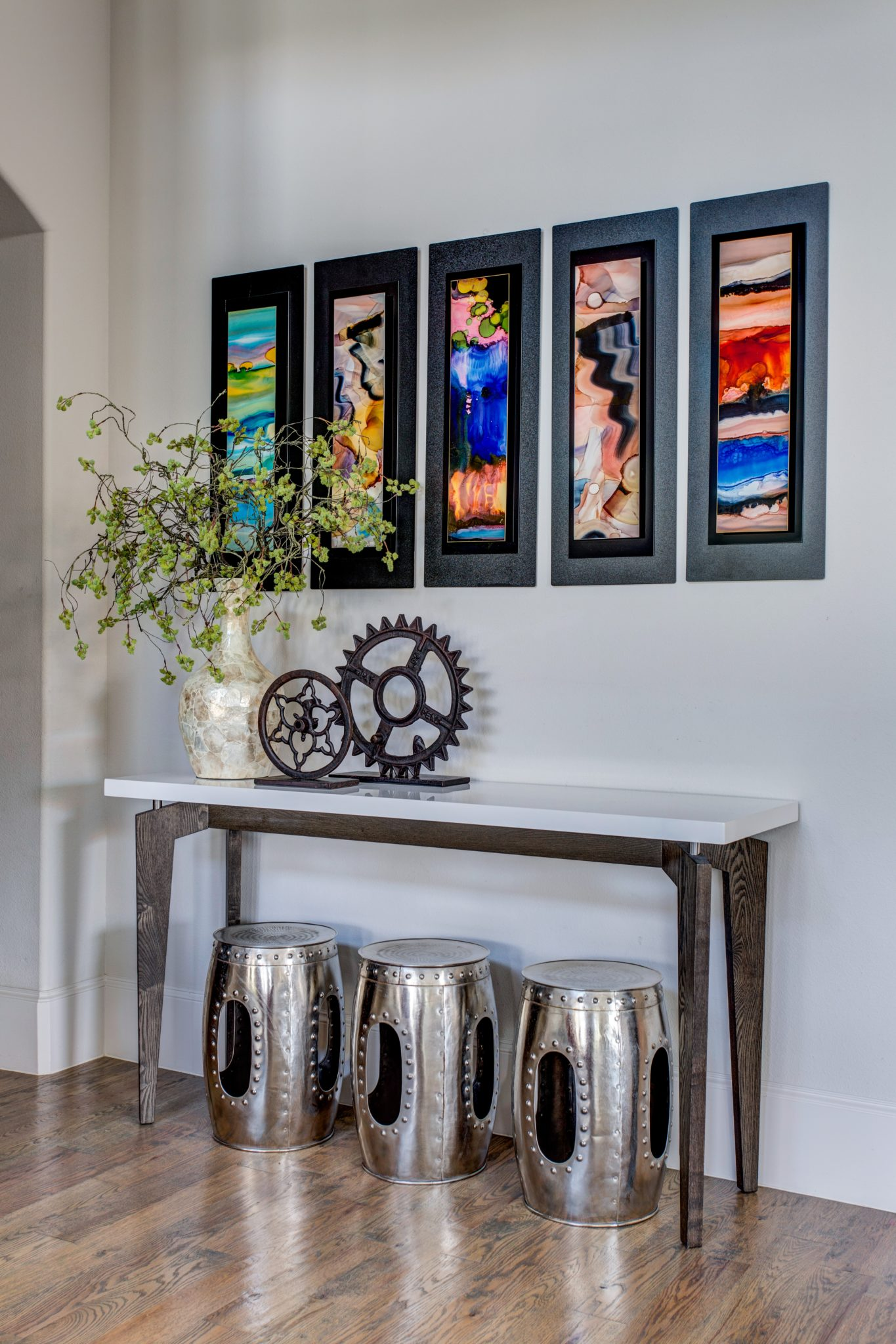 A clean console with custom art pieces and collected stools. by Wesley-Wayne Interiors