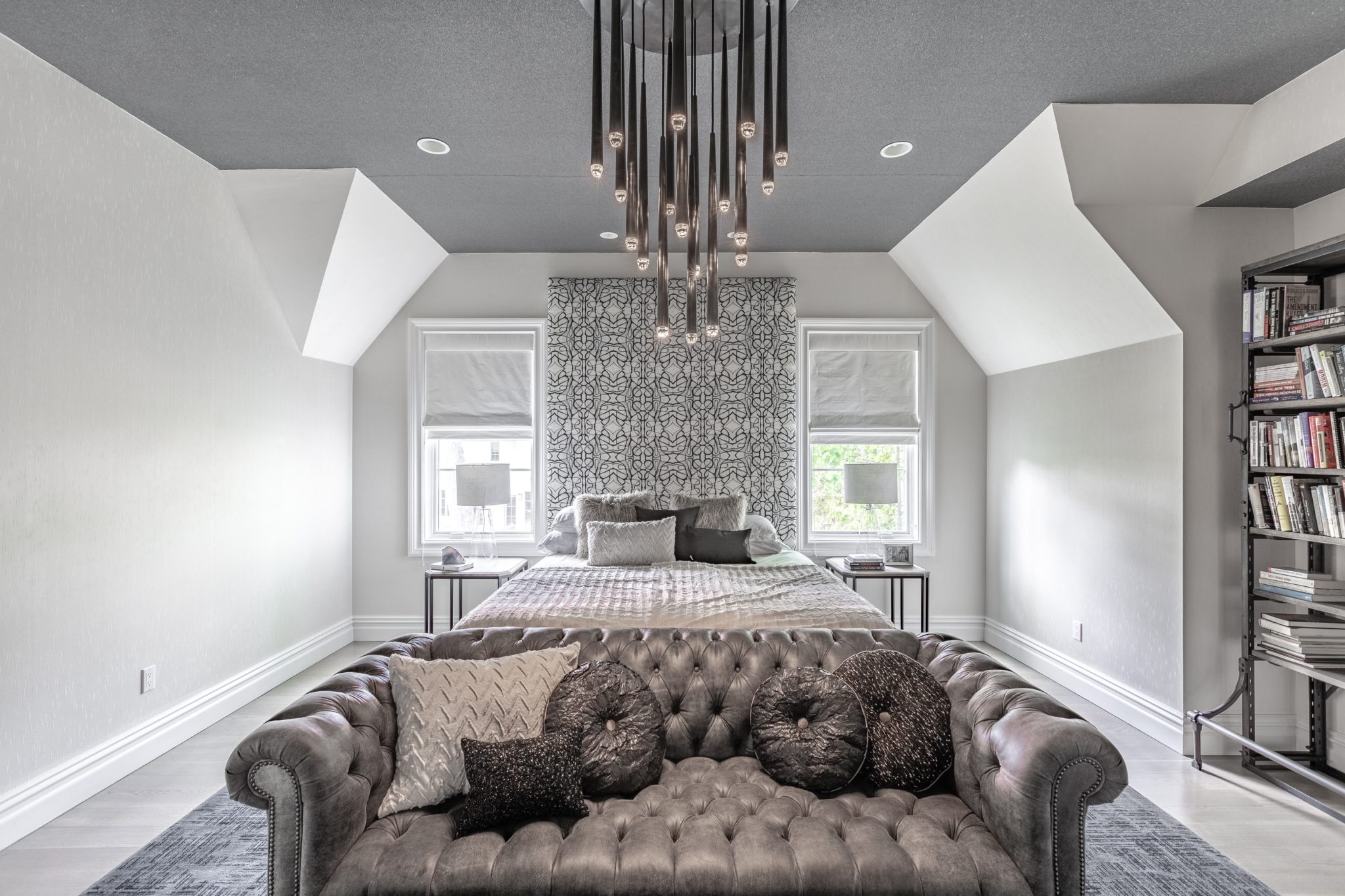 Master bedroom with vertical patterned headboard adjacent to gray leather sofa. by Shelley Cekirge Interiors
