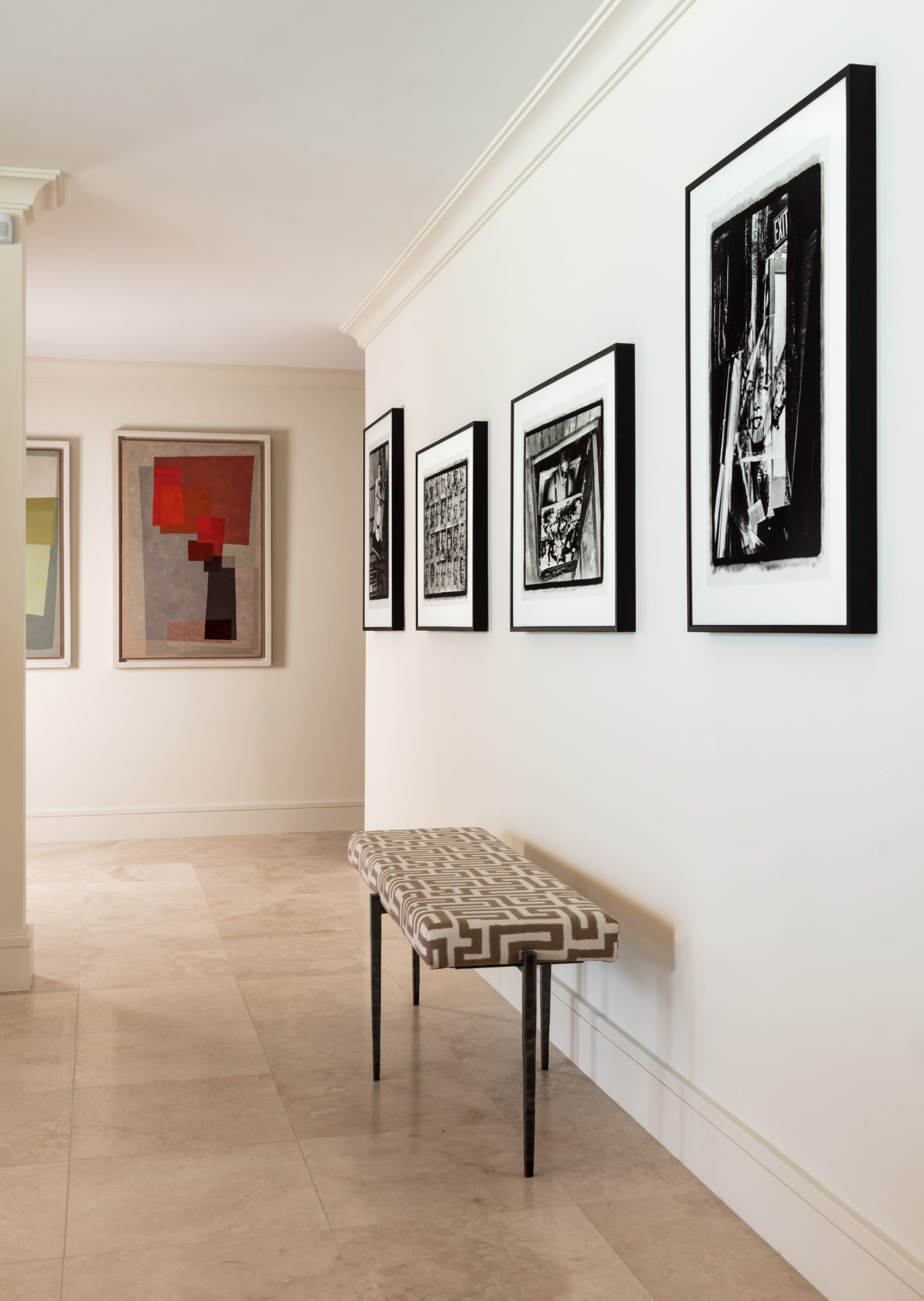 In a hallway gallery, a single bench is inspired by elongated forms. by Gil Walsh Interiors