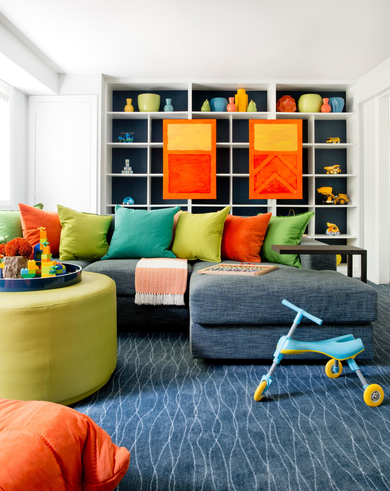 """5. Deep Blue  """"In 2017, people are embracing color, and a deep blue is an easy choice because it's practically a neutral. In this playroom, I used Sherwin Williams' Moscow Midnight (SW 9142) for the back of the bookcase. My client and I both loved rich blue-greens, and the deep saturation of this vibrant hue grounds the bright tones in the room and adds a graphic backdrop to the accessories and toys.""""  Caroline Kopp, ofCaroline Kopp Interior Design"""
