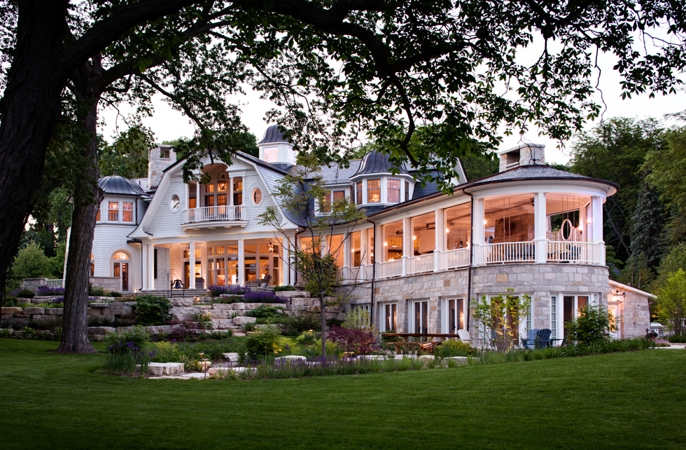 Grey shingle-style family Lake House with entertaining porch wing by Wade Weissmann Architecture Inc.