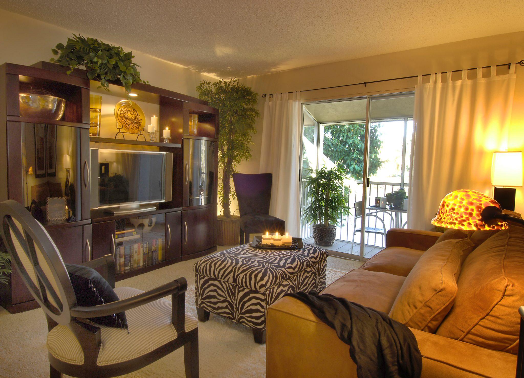 Small space condo living room, zebra ottoman, tortoise shell lamp and TV wall unit by Barbara Krai Interior Design