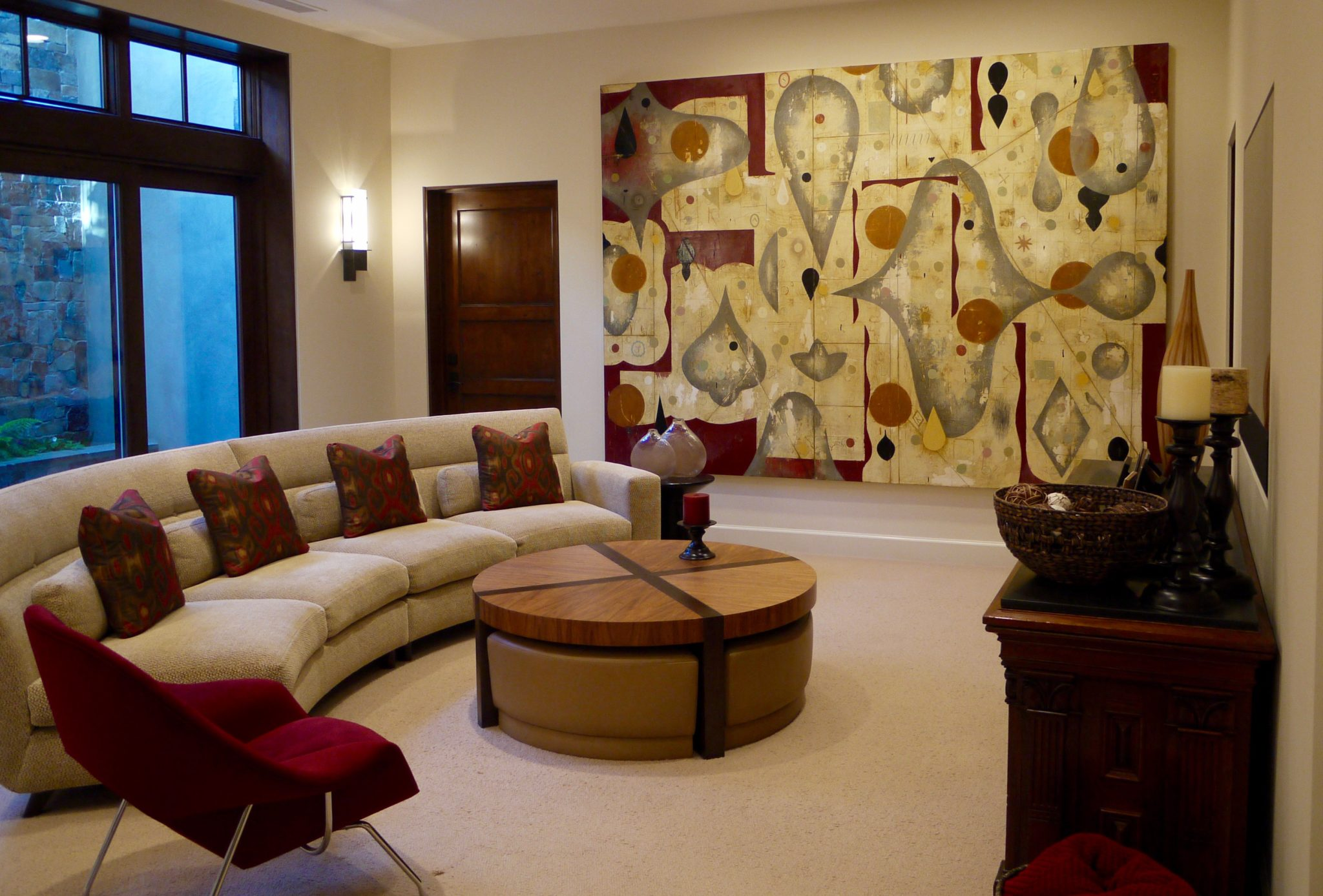 Family Room features original art, curved sofa and cocktail table with ottomans by Alison Whittaker Design