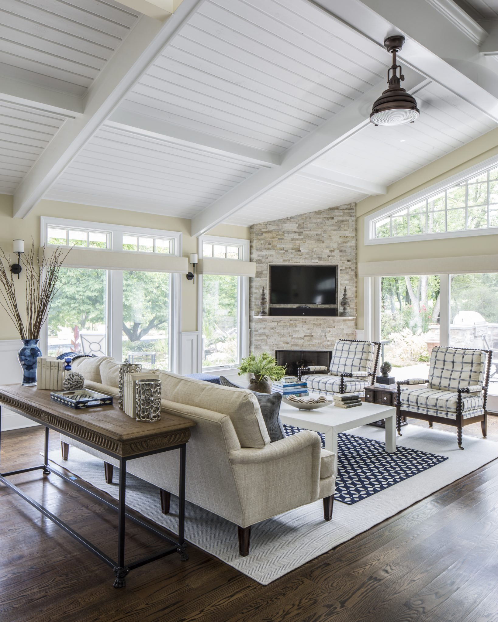 Great room with wall of windows overlooking yard with transoms and ceiling detail by Kim Radovich, Kim E. Courtney Interiors