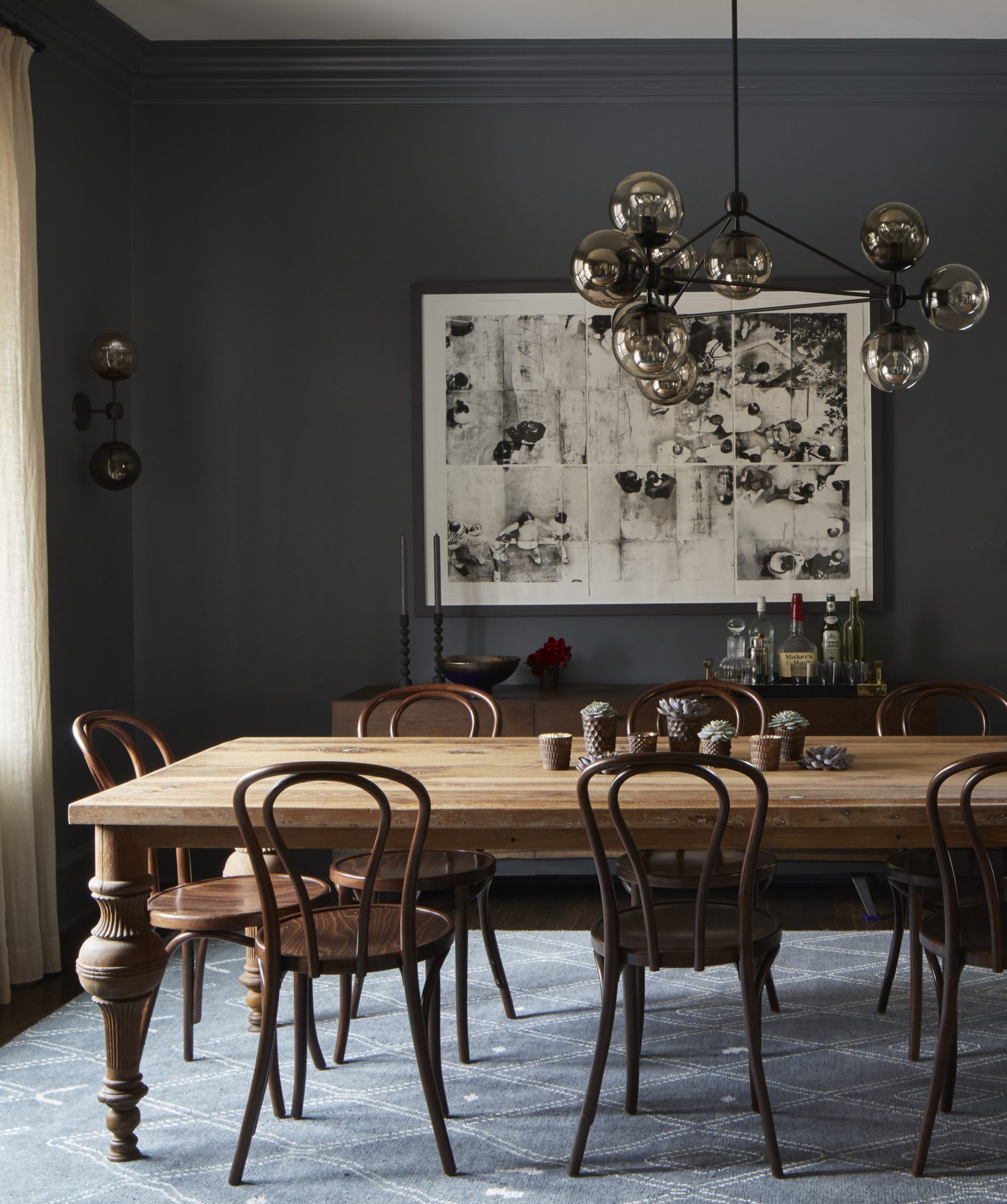 Dining room with dark walls and modern lighting by 2to5 Design