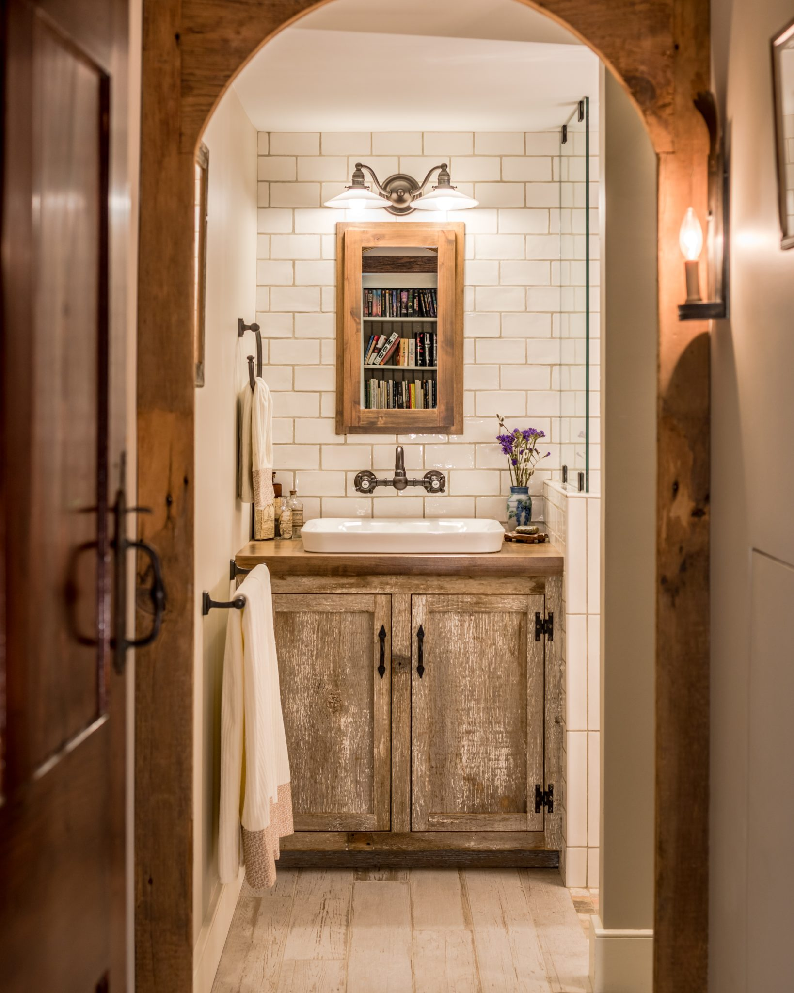 Rustic farmhouse bathroom with natural wood and white tile by Period Architecture