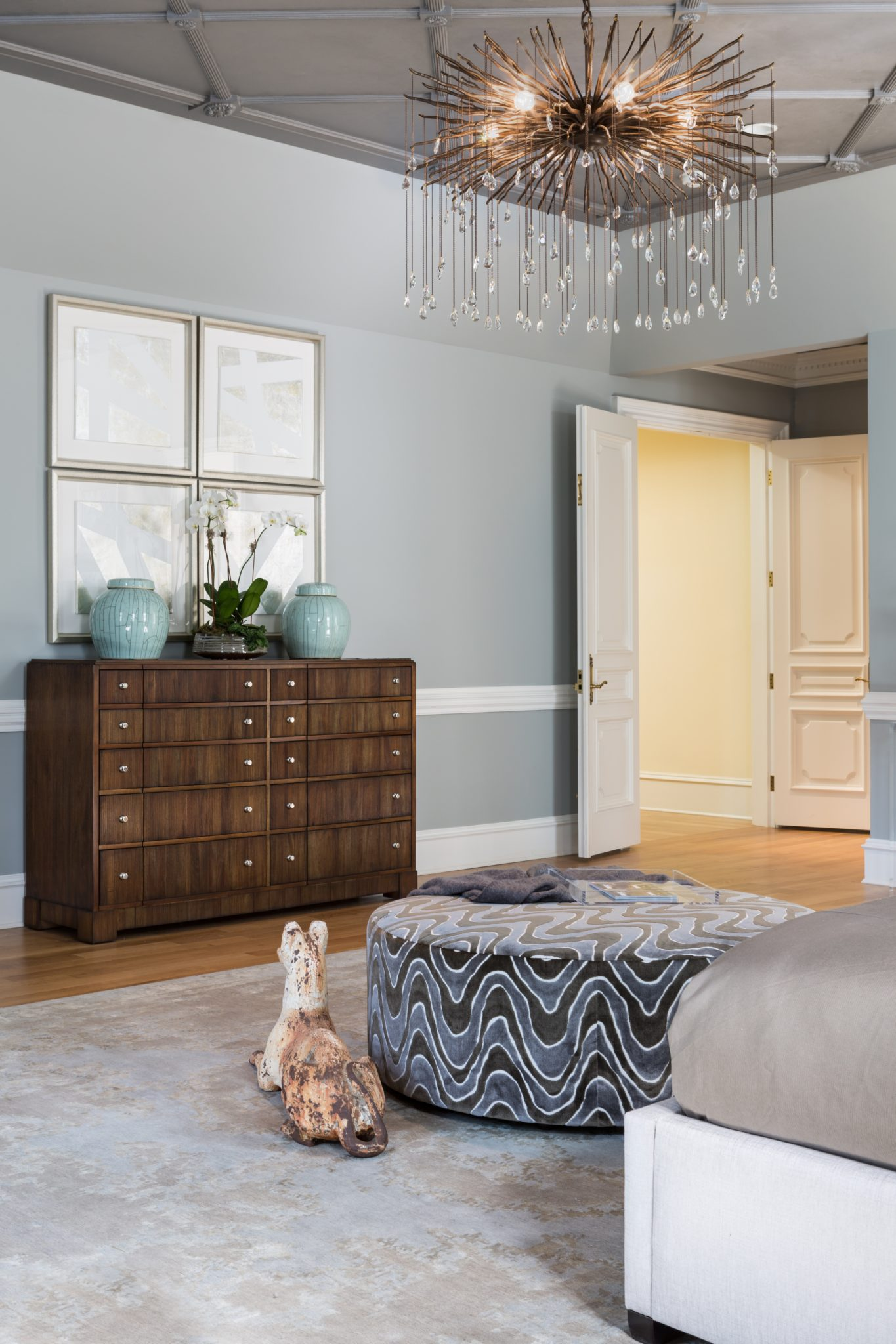 Master suite anchored by a swirling ottoman + chandelier on a metallic ceiling by Interiors by Design