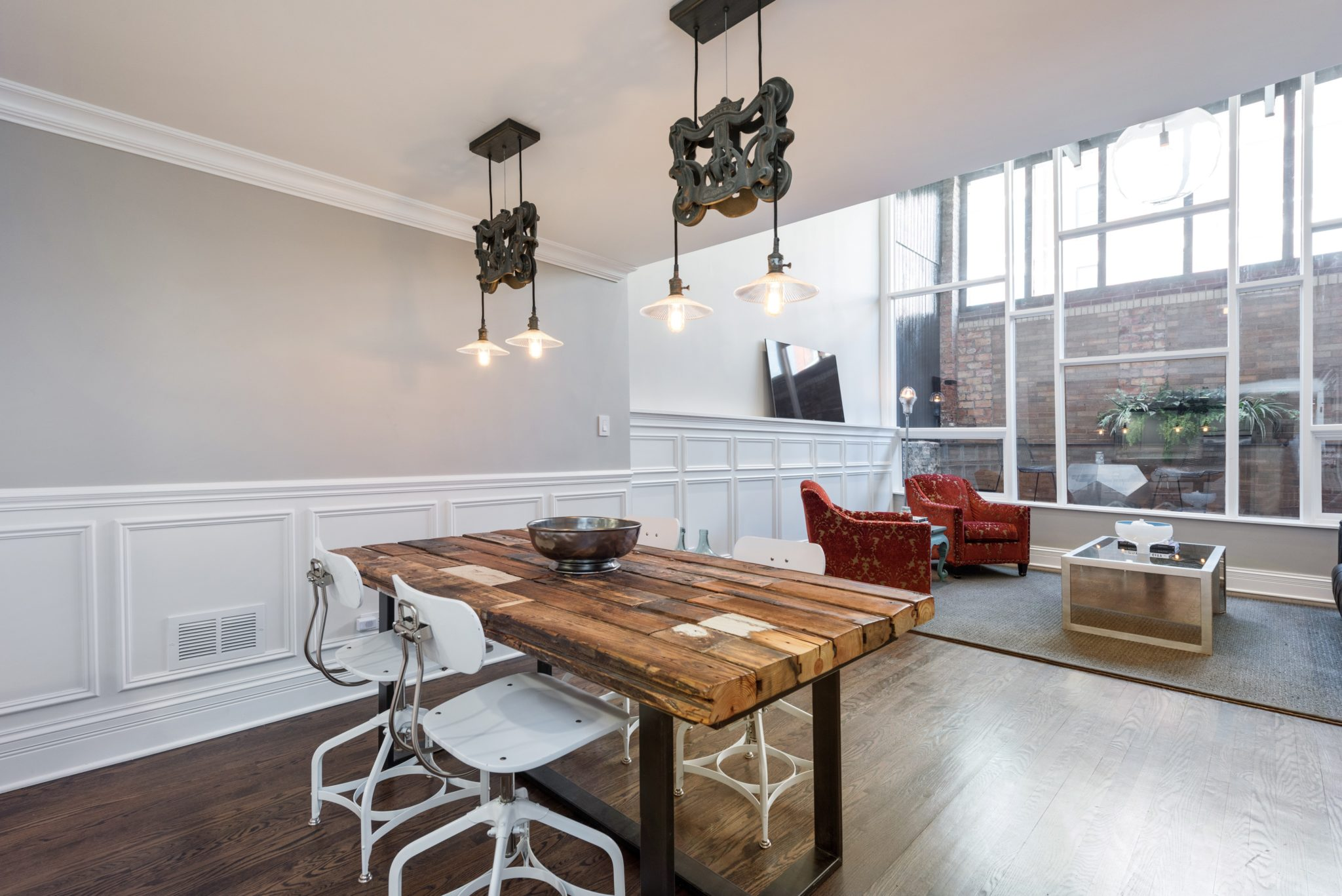 Industrial condo - dining room with raw wood table and white wainscoting by Rae Duncan Interior Design