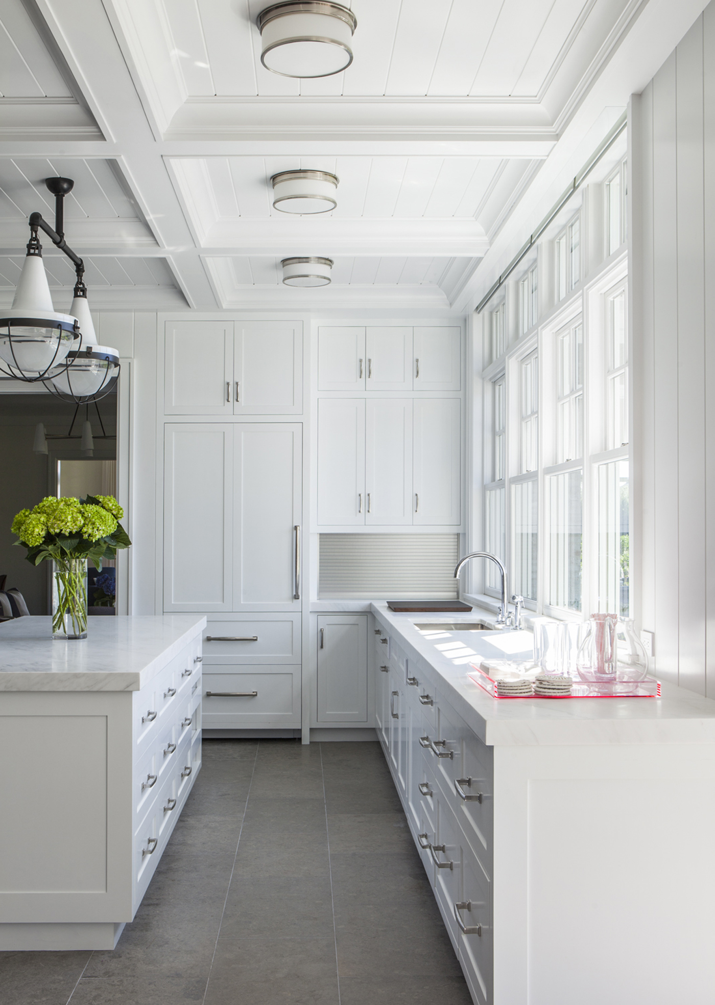 Hamptons Residence, open Kitchen w/ minimal white palette and coffered ceiling by Stephens Design Group
