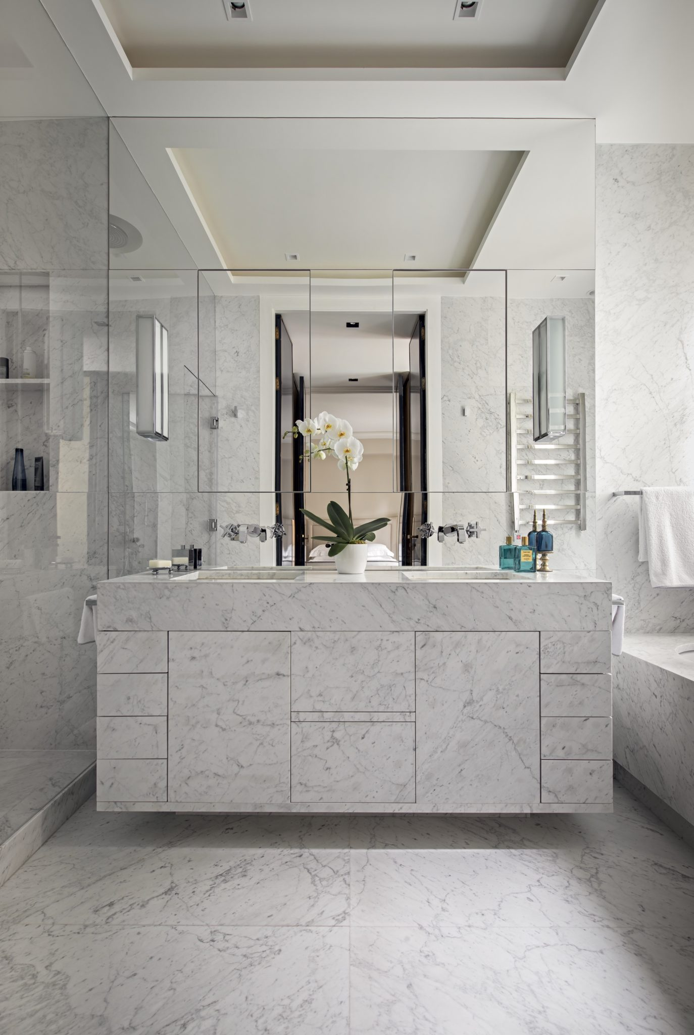A master bathroom in marble and mirrors by Champeau & Wilde