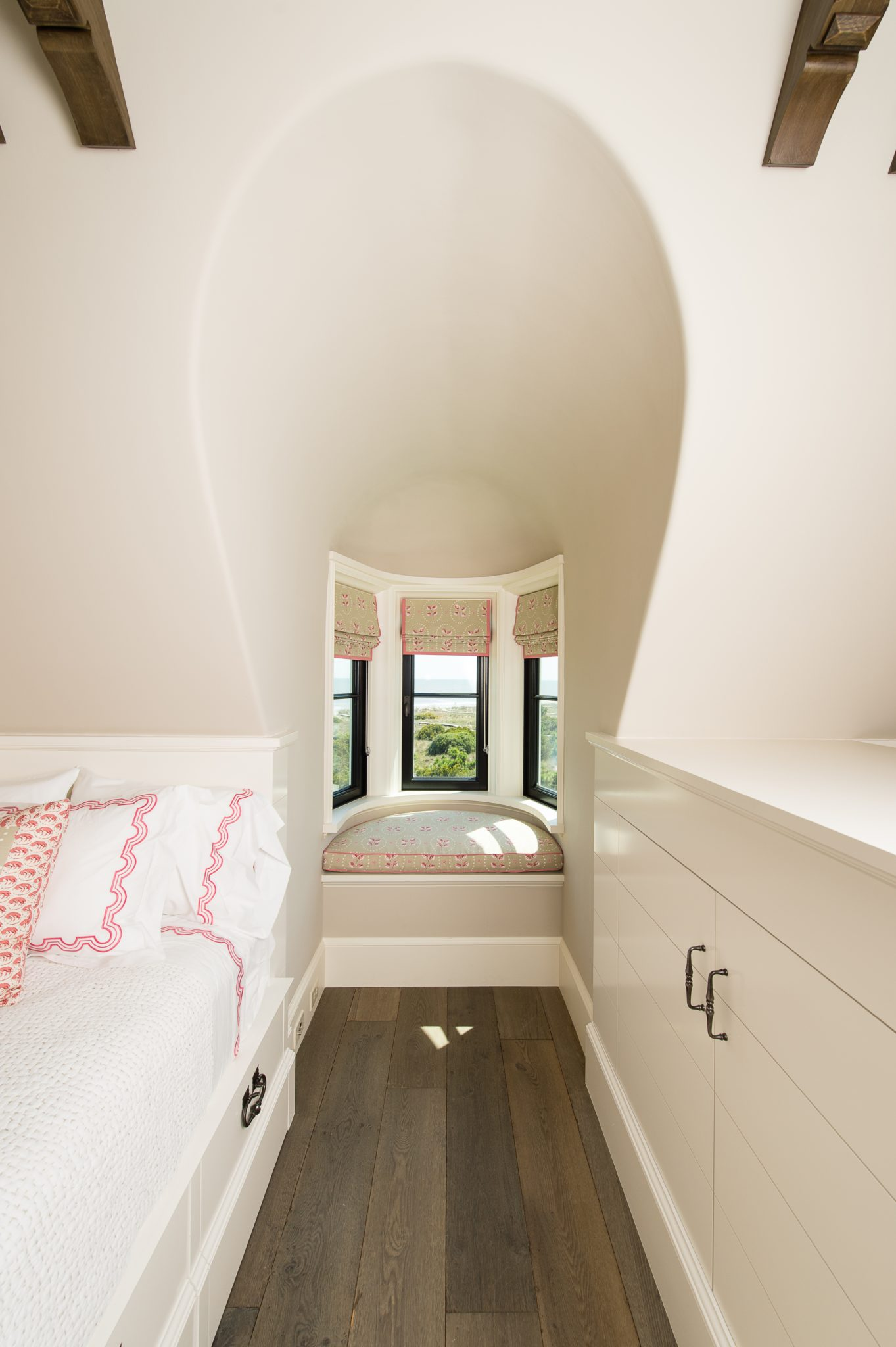 Bunk room curved bay window seat and dormer with built-in cabinets by Island Architects