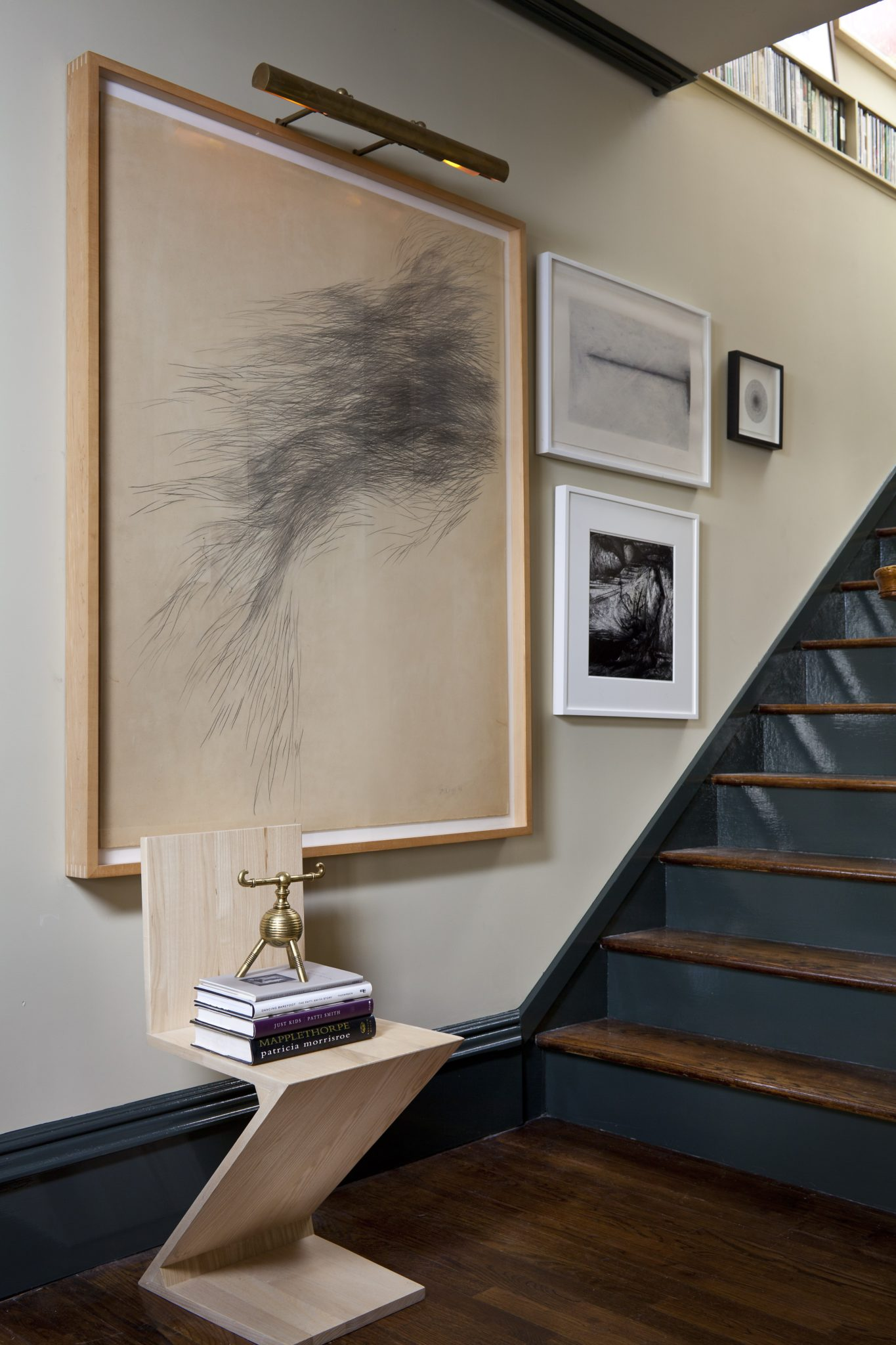 Eclectic art-filled stairwell in a townhouse by Glenn Gissler