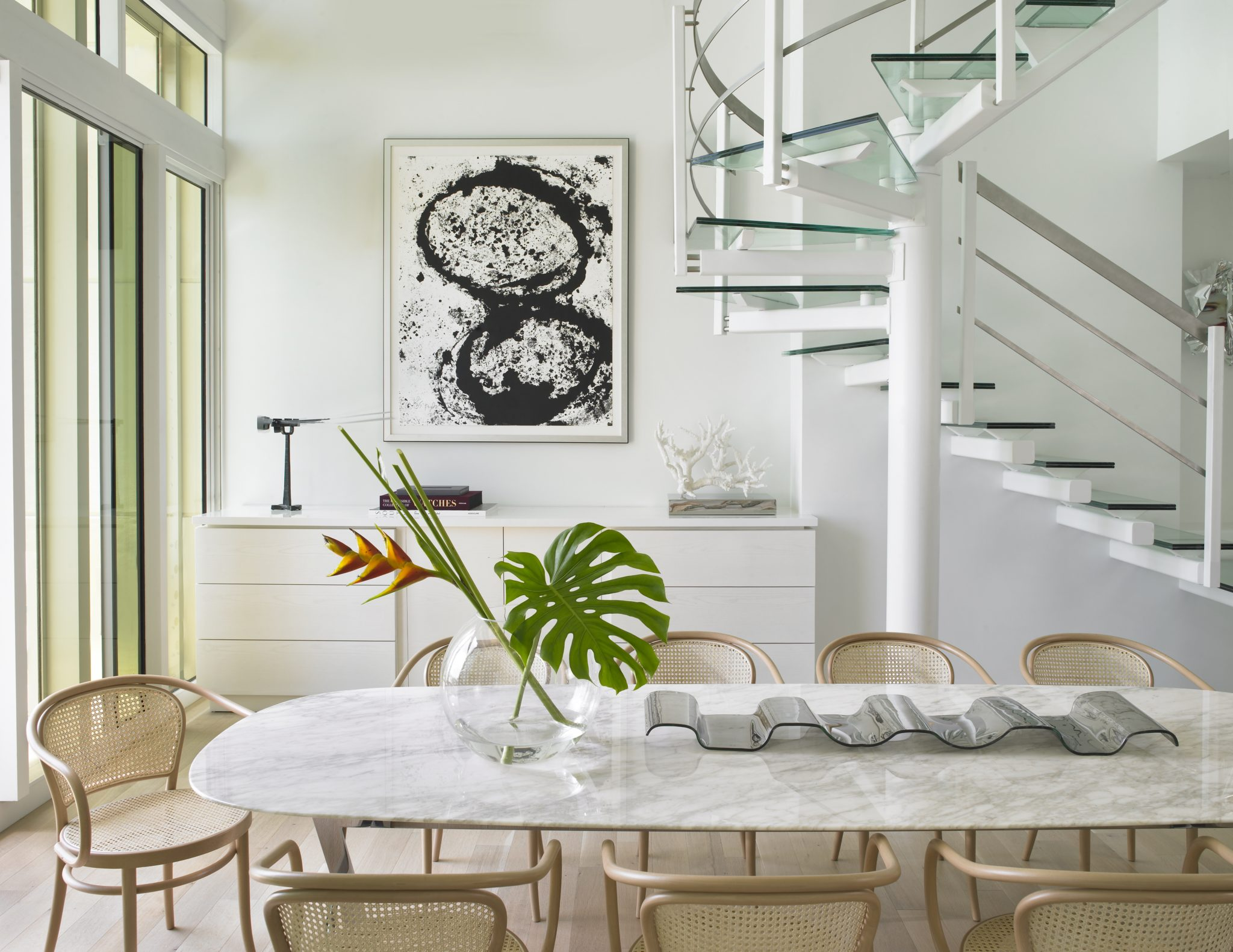Basket-weave chairs surround the table in the casual dining area. Custom-designed cabinetry beneath the staircase has the same recessed edge as the walls to give the illusion that it is floating in the space. By Michael Wolk Design Associates