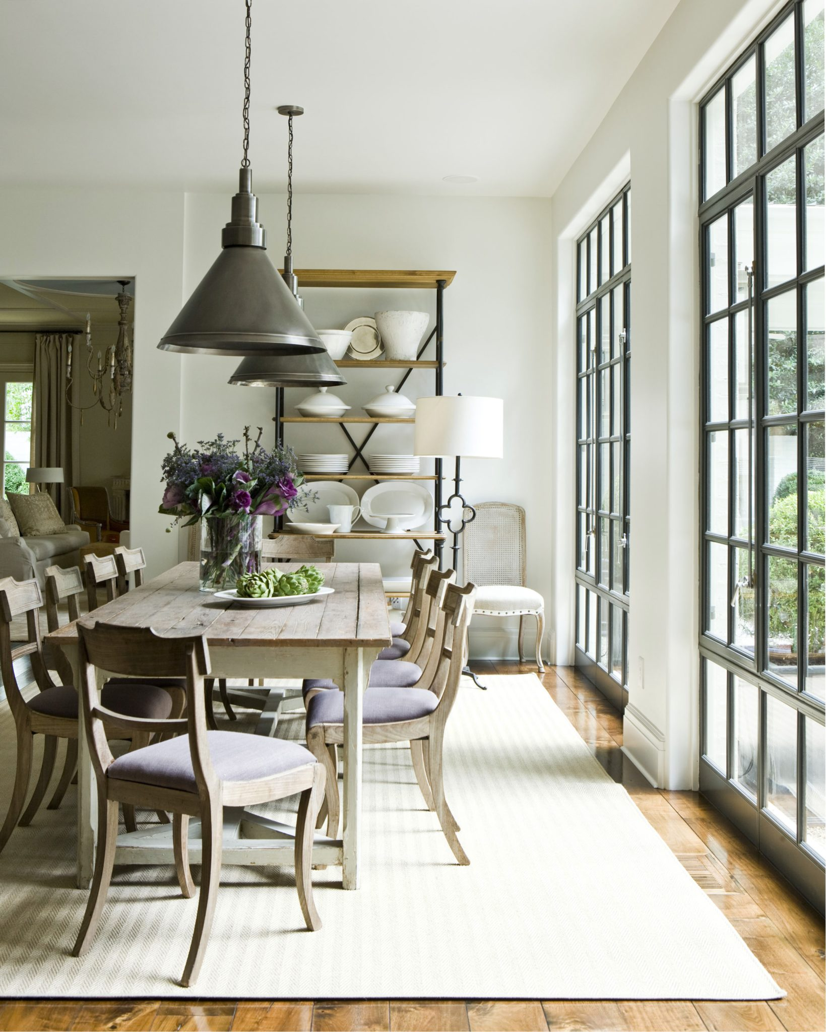 Dining room with large windows by Suzanne Kasler Interiors