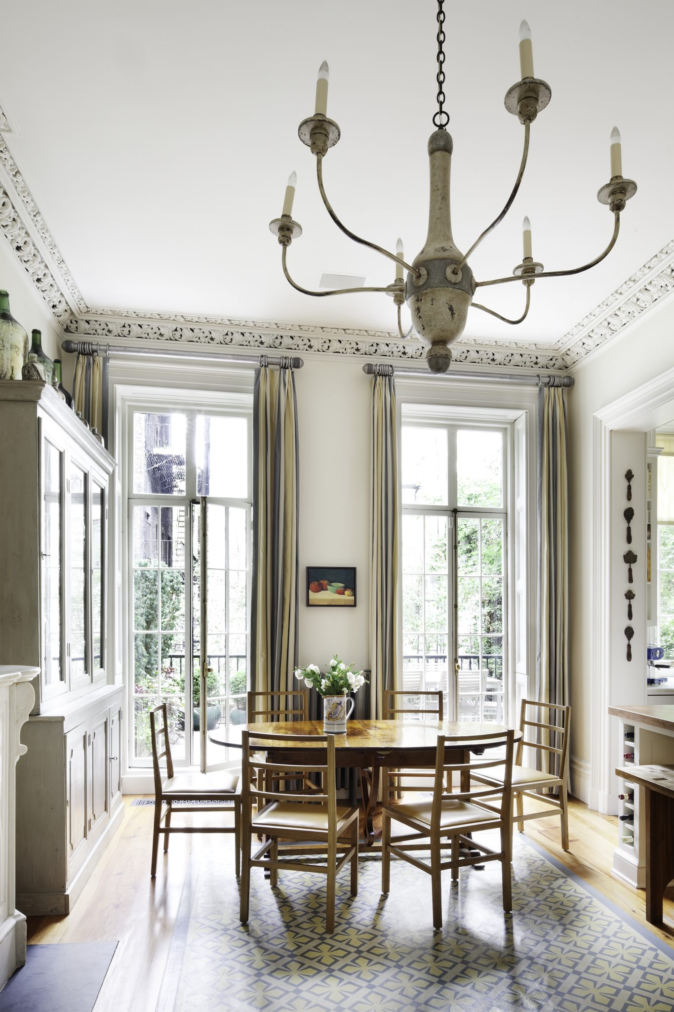 Townhouse dining room with natural light andfloor-to-ceiling windows by Sheila Bridges Design Inc.