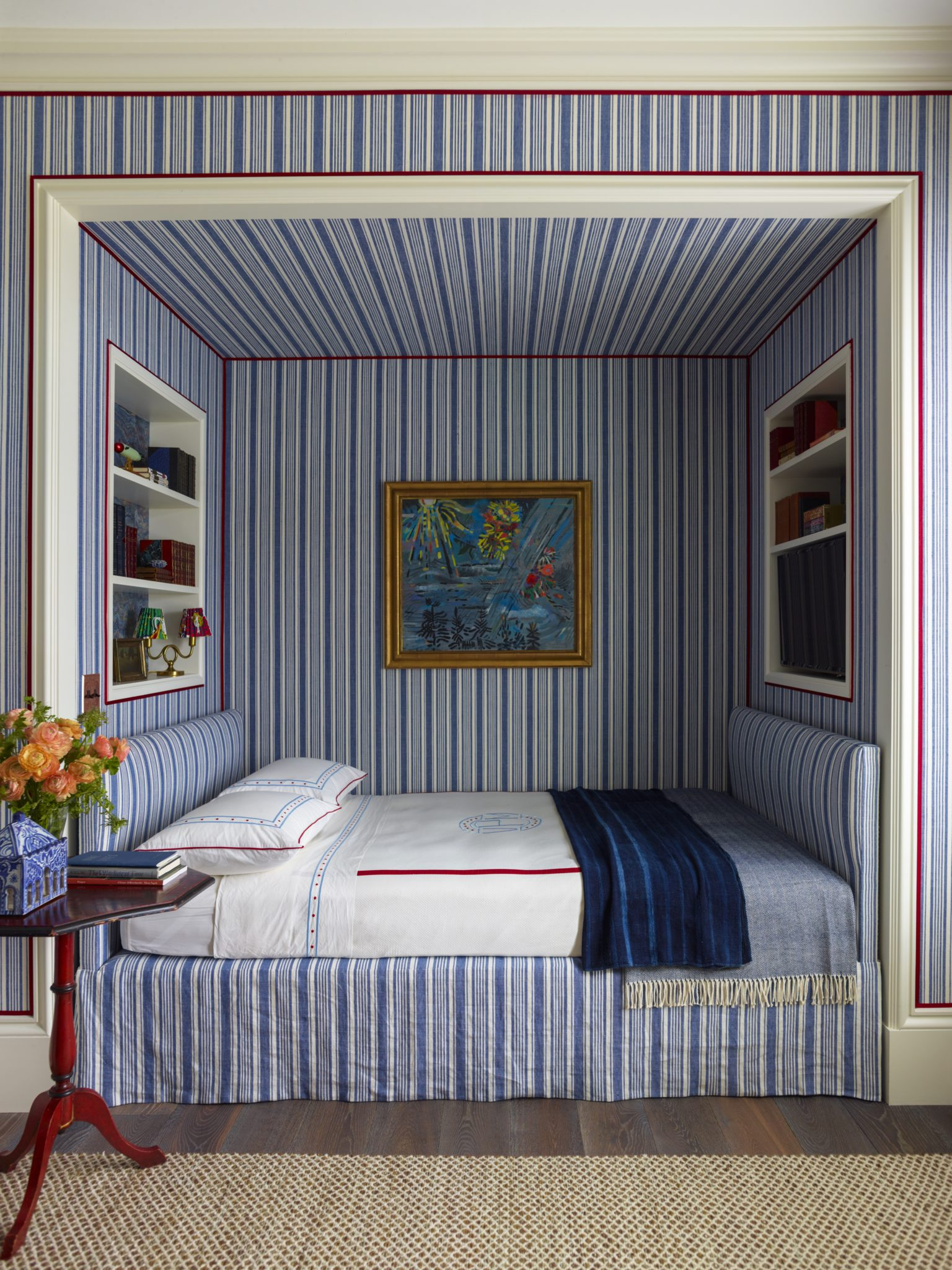Built-in bed with shelving and blue striped wallpaper by Katie Ridder Inc.