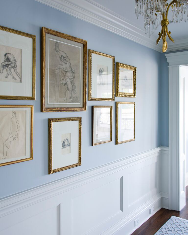 A hallway sports a classic combination of brass and blue. by Diana Sawicki Interior Design Inc.