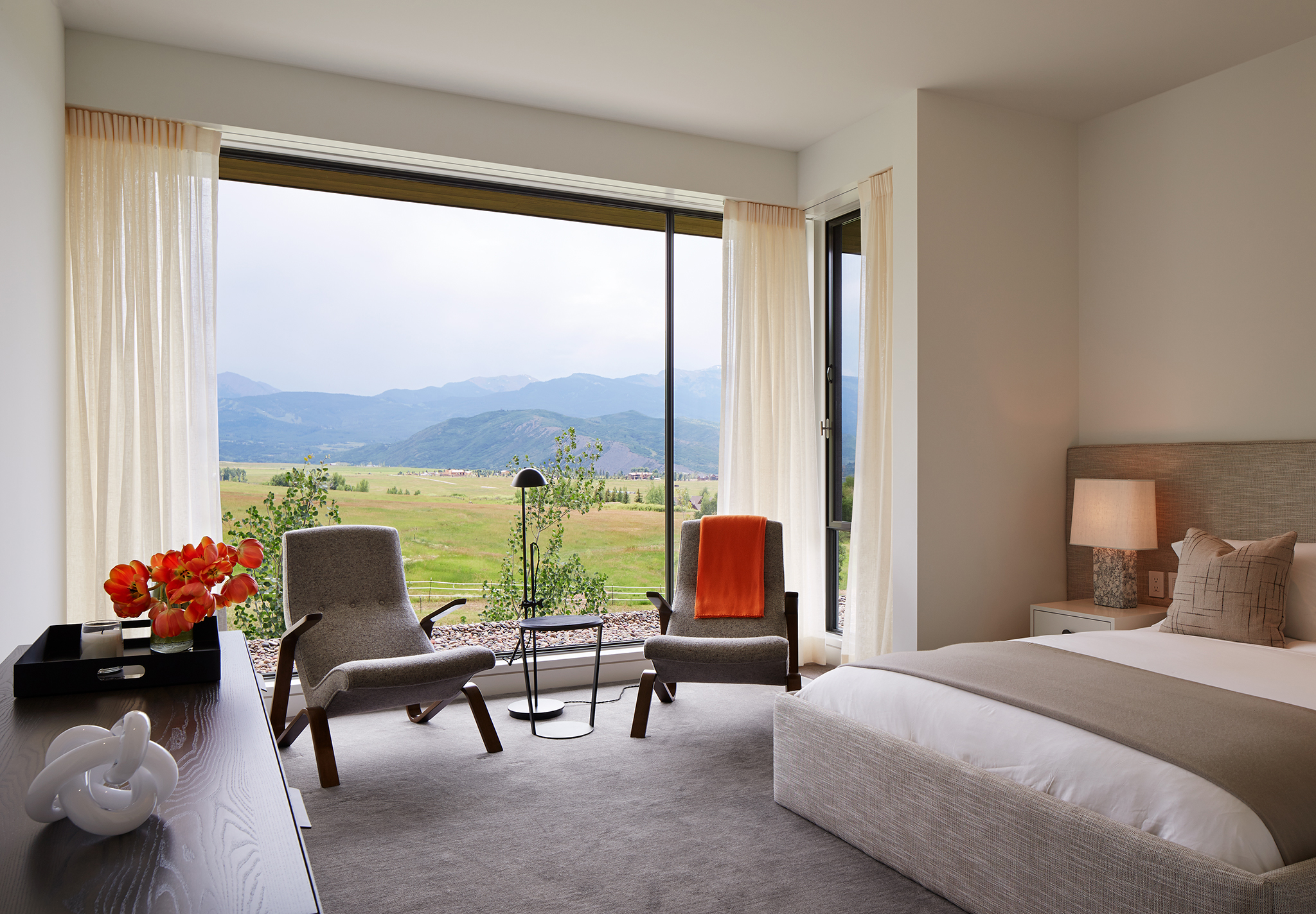 Second floor bedroom with floor-to-ceiling window to capture dramatic mountain view. By Robbins Architecture