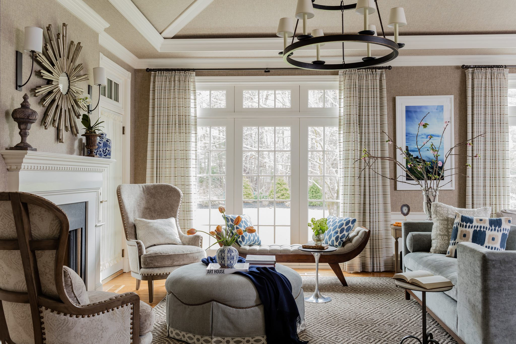 Neutralliving room withvaulted ceiling andtwo-tier chandelier by Robin Gannon Interiors