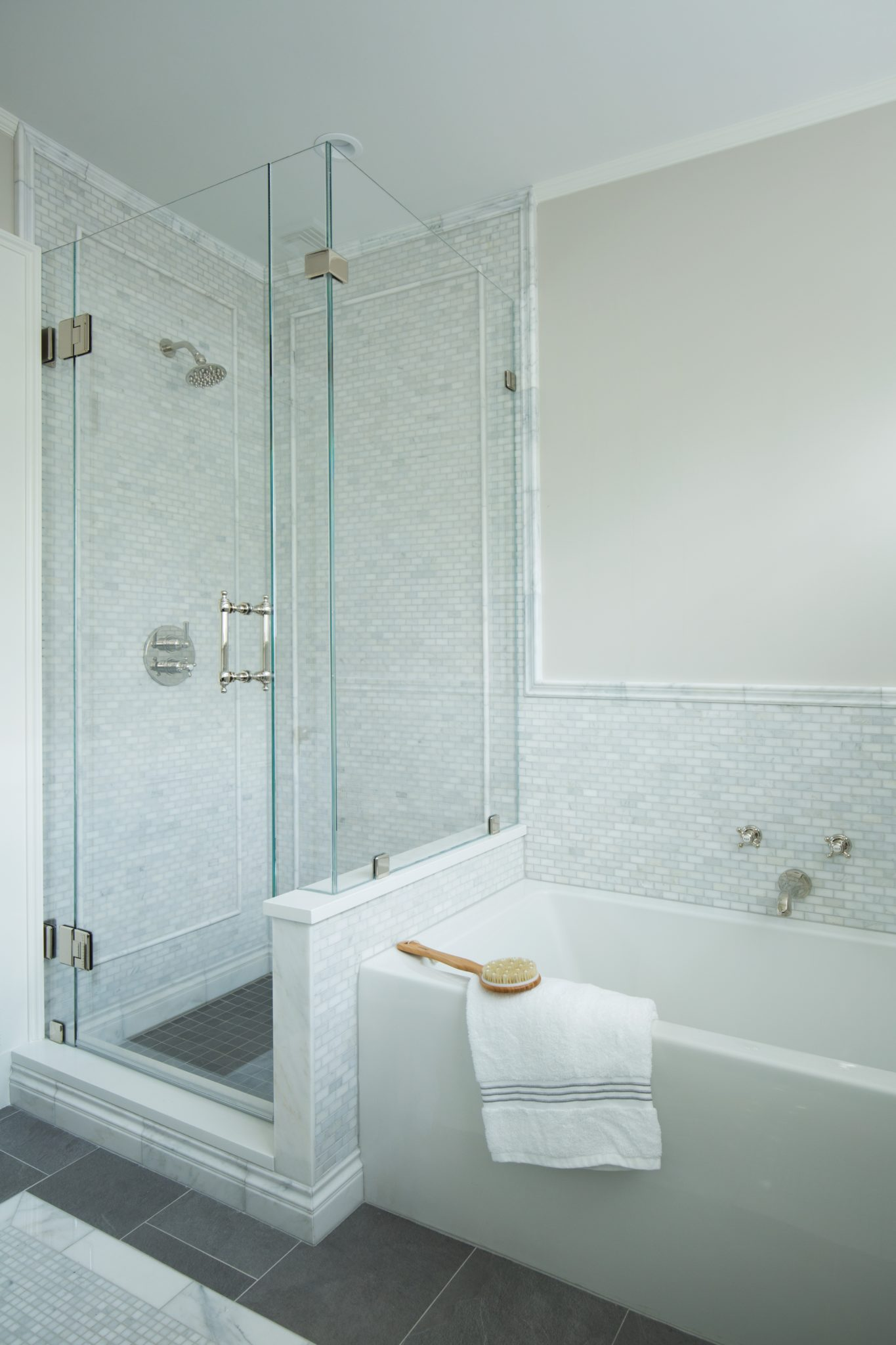 Marble mosaic tile walk-in shower and soaking tub by CW Design, LLC