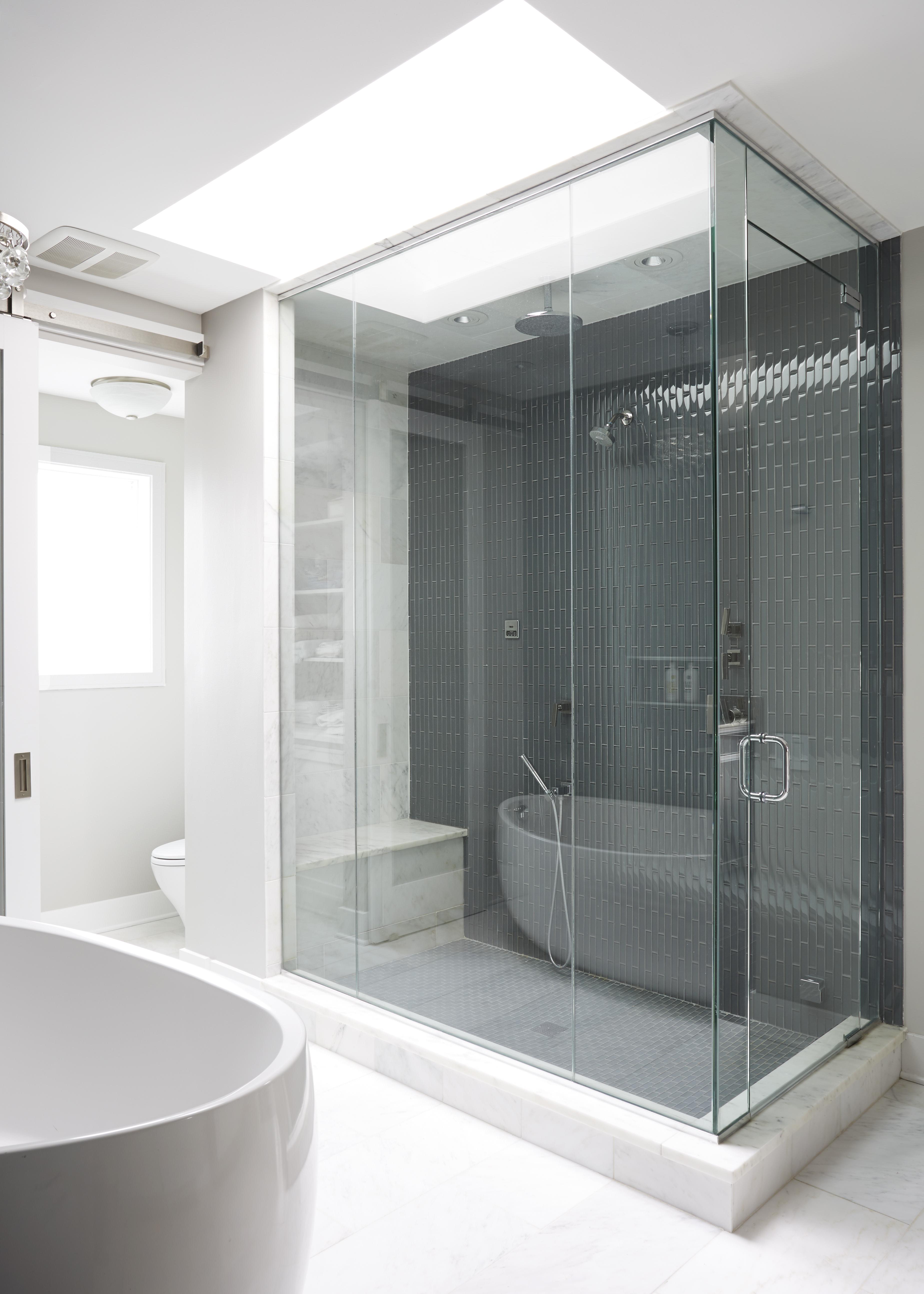 Modern condo master bathroom, blue tile shower, marble, skylight by Maren Baker Design