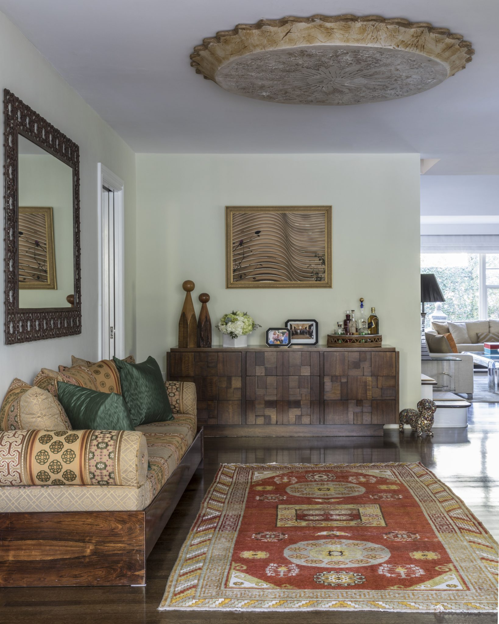 Family room with Moroccan mirror, vintage buffet and bench upholstered in Moroccan-style fabric. By Michele Safra Interiors
