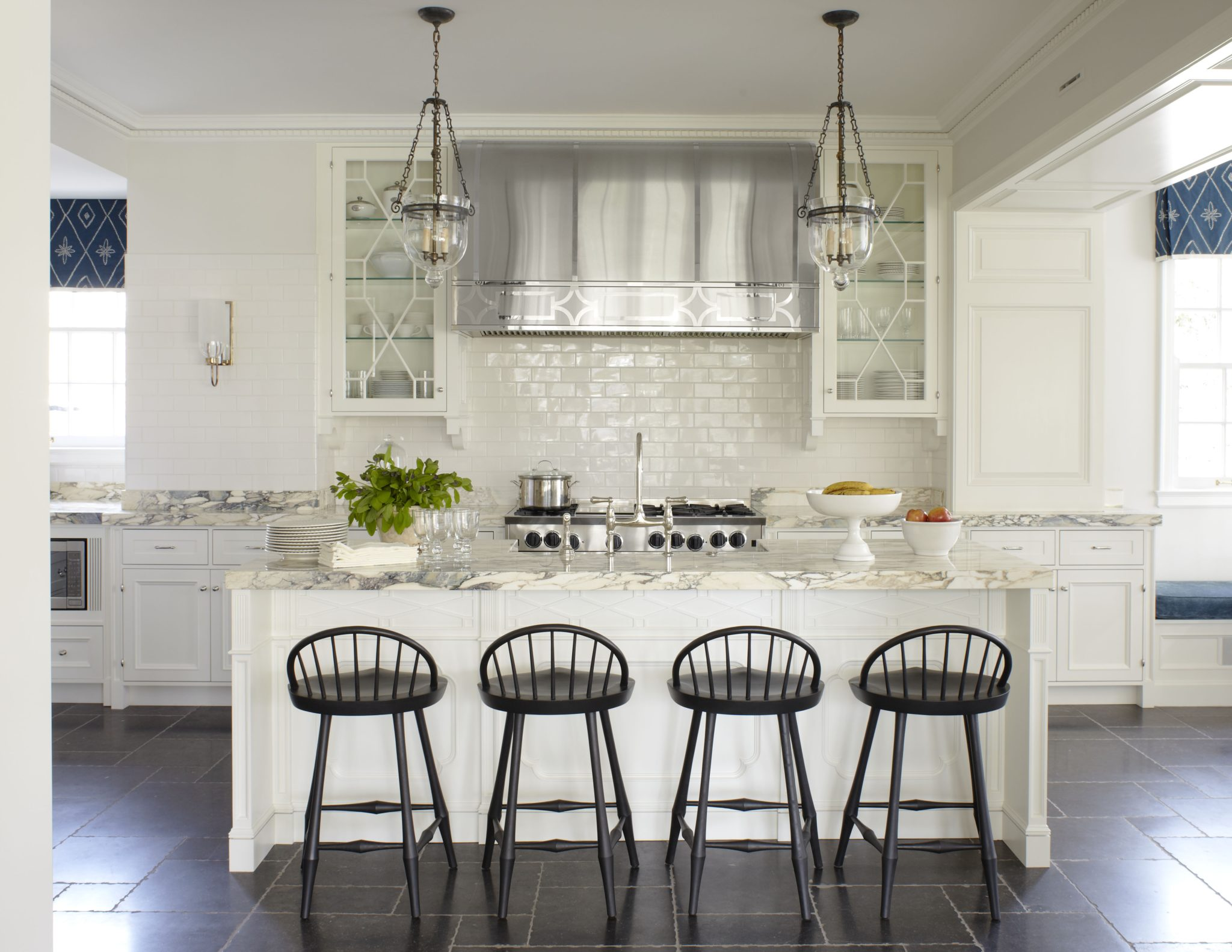Extra large kitchen with island and bar seating, pendant lighting and subway tile. By James Michael Howard