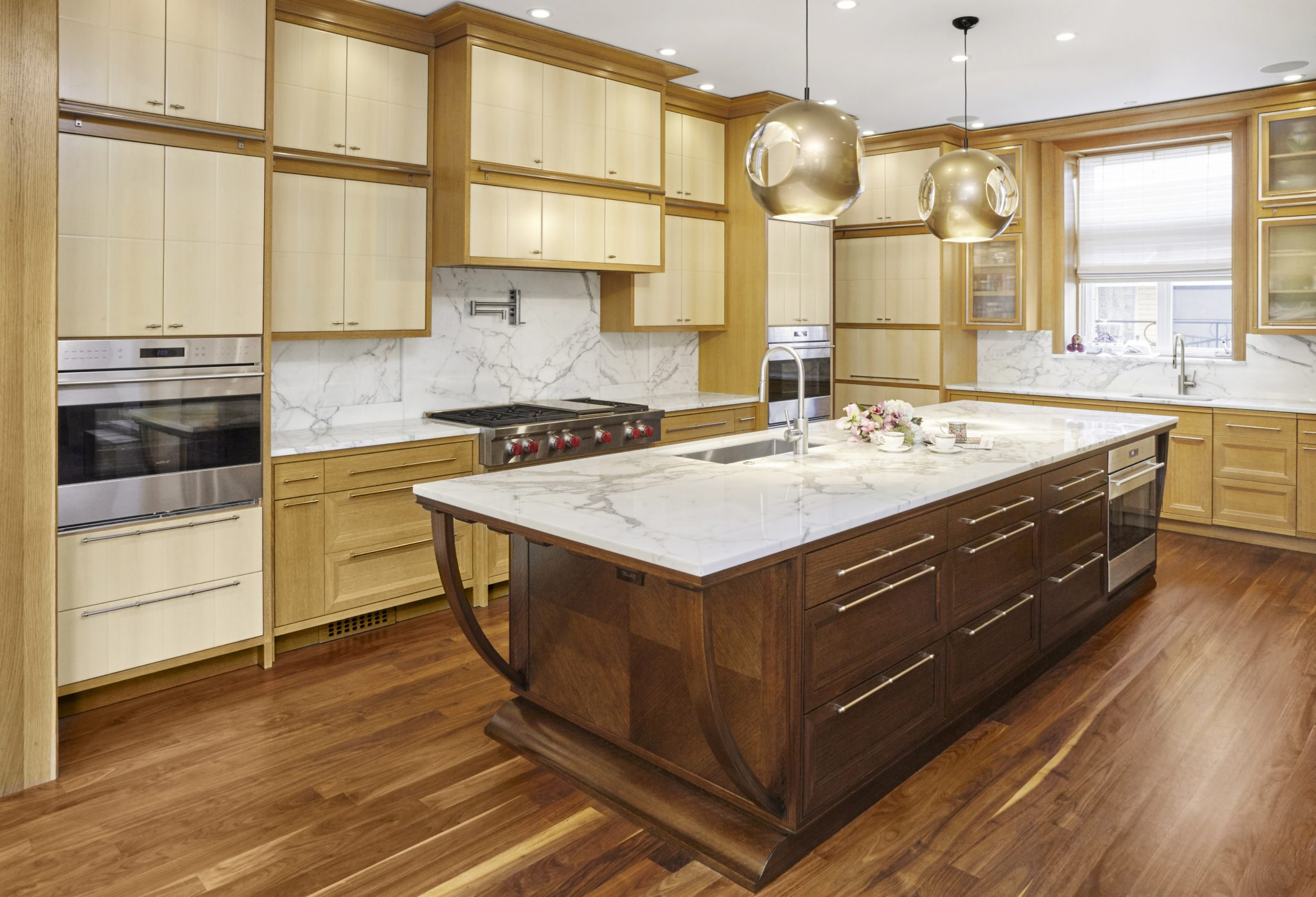 Art Deco kitchen with oak and birch cabinets, marble countertop and backsplash by Randall Architects, Inc.
