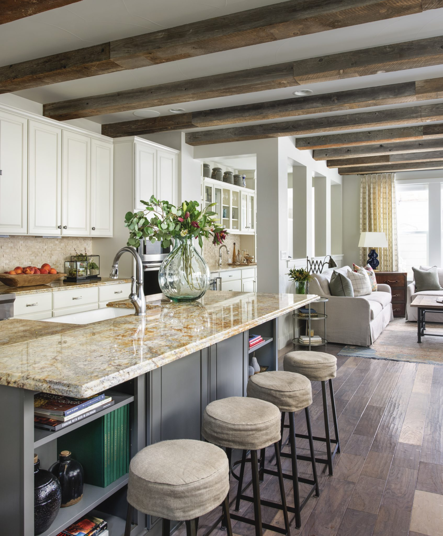 Traditional farmhouse kitchen with island bar seating by Duet Design Group