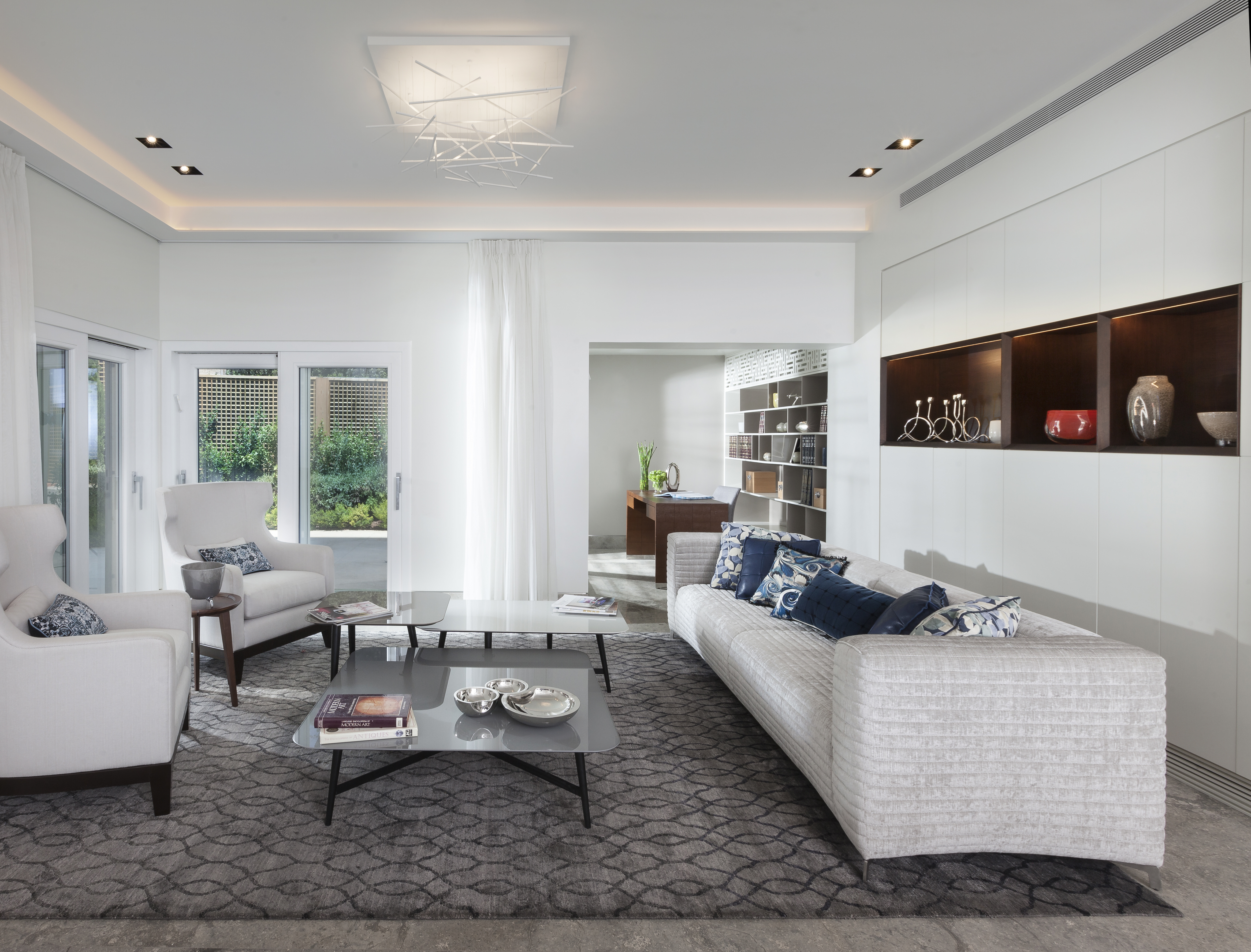 A living room in modern garden apartment with soothing color palette, grey sofa. by Annette Frommer Interior Design