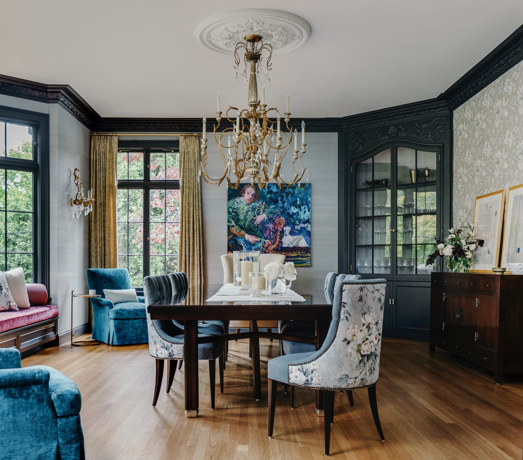 Blue and purple dining room with dark wood table and brass chandelier. by IDF Studio