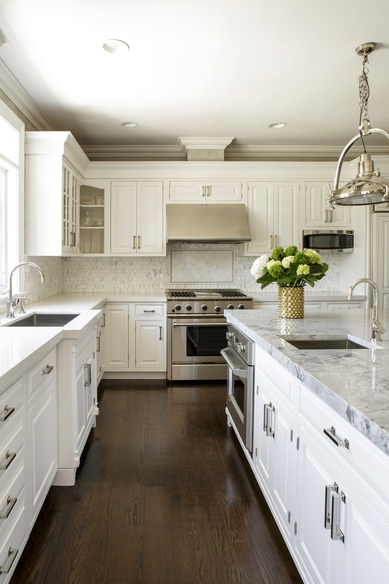 Traditional transitional kitchen with white cabinets, marble countertops and dark flooring by Laura Michaels Design