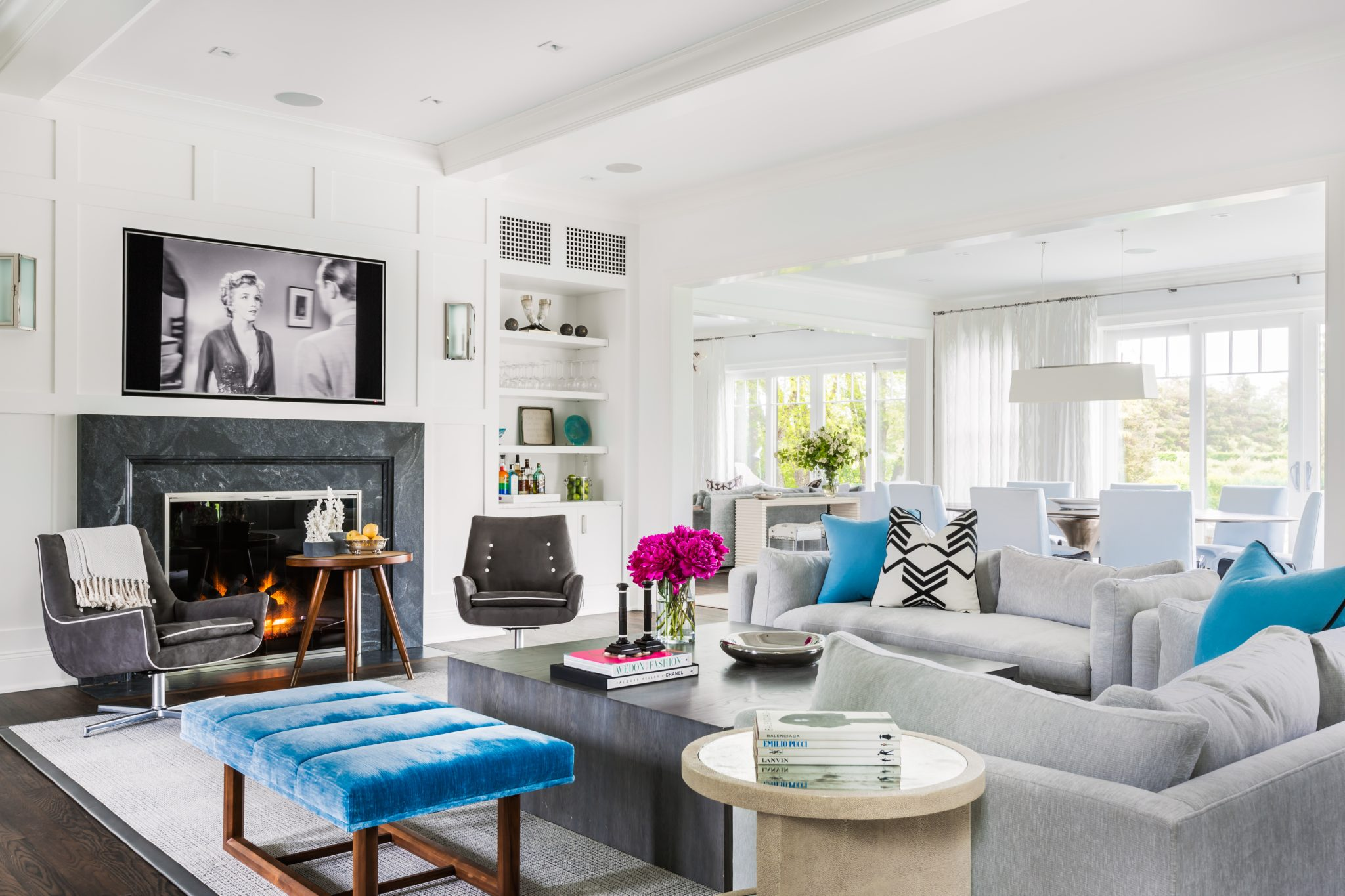 Transitional Living Room with Paneled Walls, Turquoise Accents, and Modern Stone Mantel by Alisberg Parker Architects
