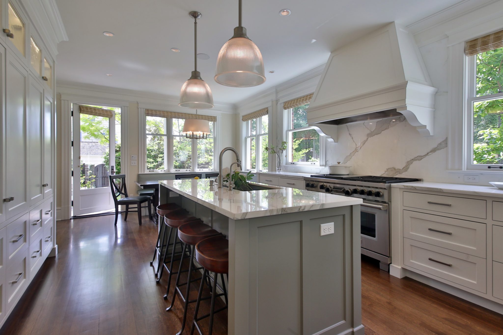 Seattle kitchen with grey island, white cabinets and hood, and marble backsplash by LeeAnn Baker Interiors Ltd.