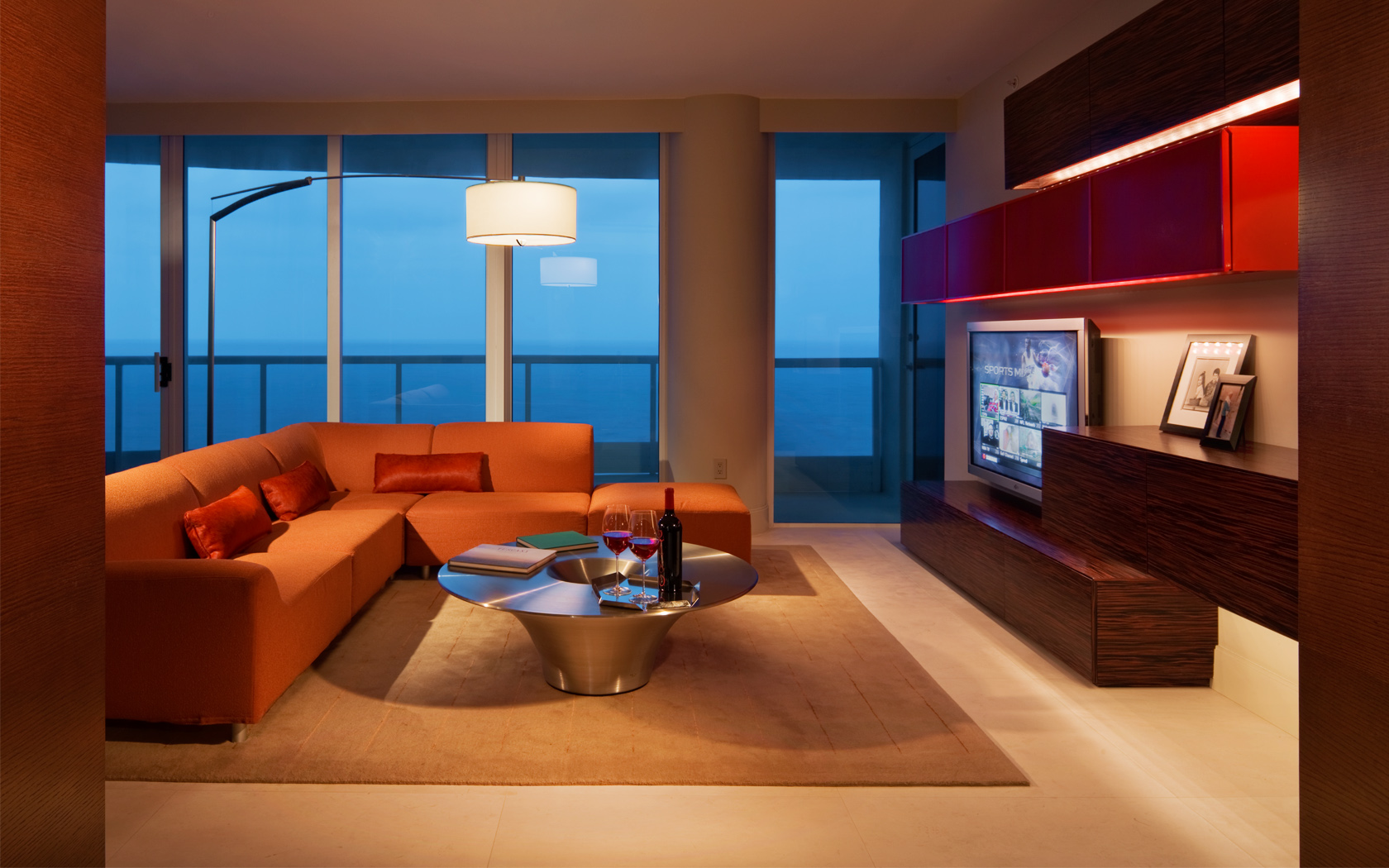 The interior design is modern with a warmth created by a wood paneled ceiling. by Michael Wolk Design Associates