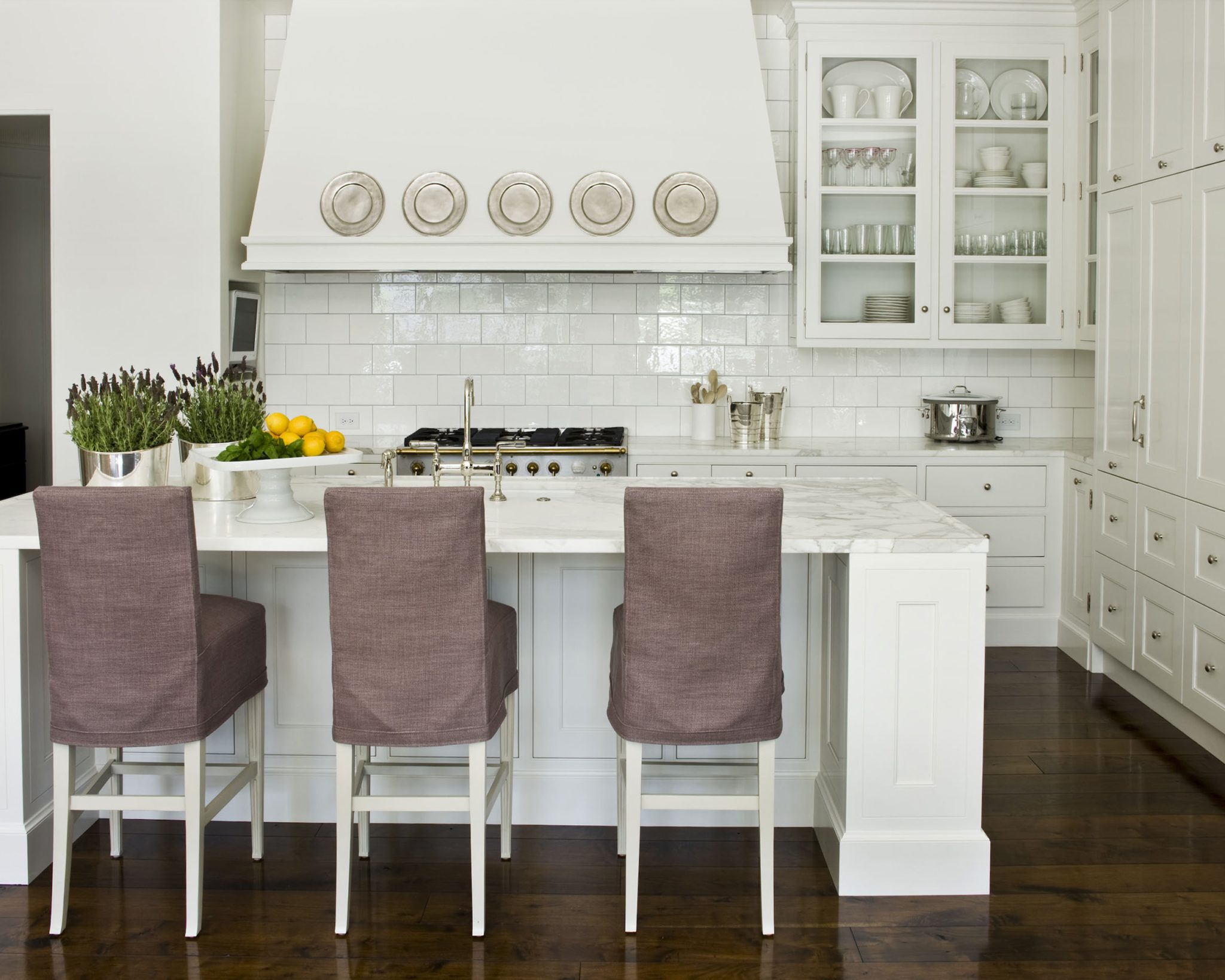 At Home kitchen with subway tile, breakfast bar by Suzanne Kasler Interiors
