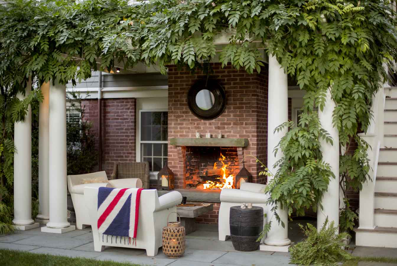 Trellis-covered outdoor living space with fireplace and Philippe Starck chairs by Kristin Paton Interiors