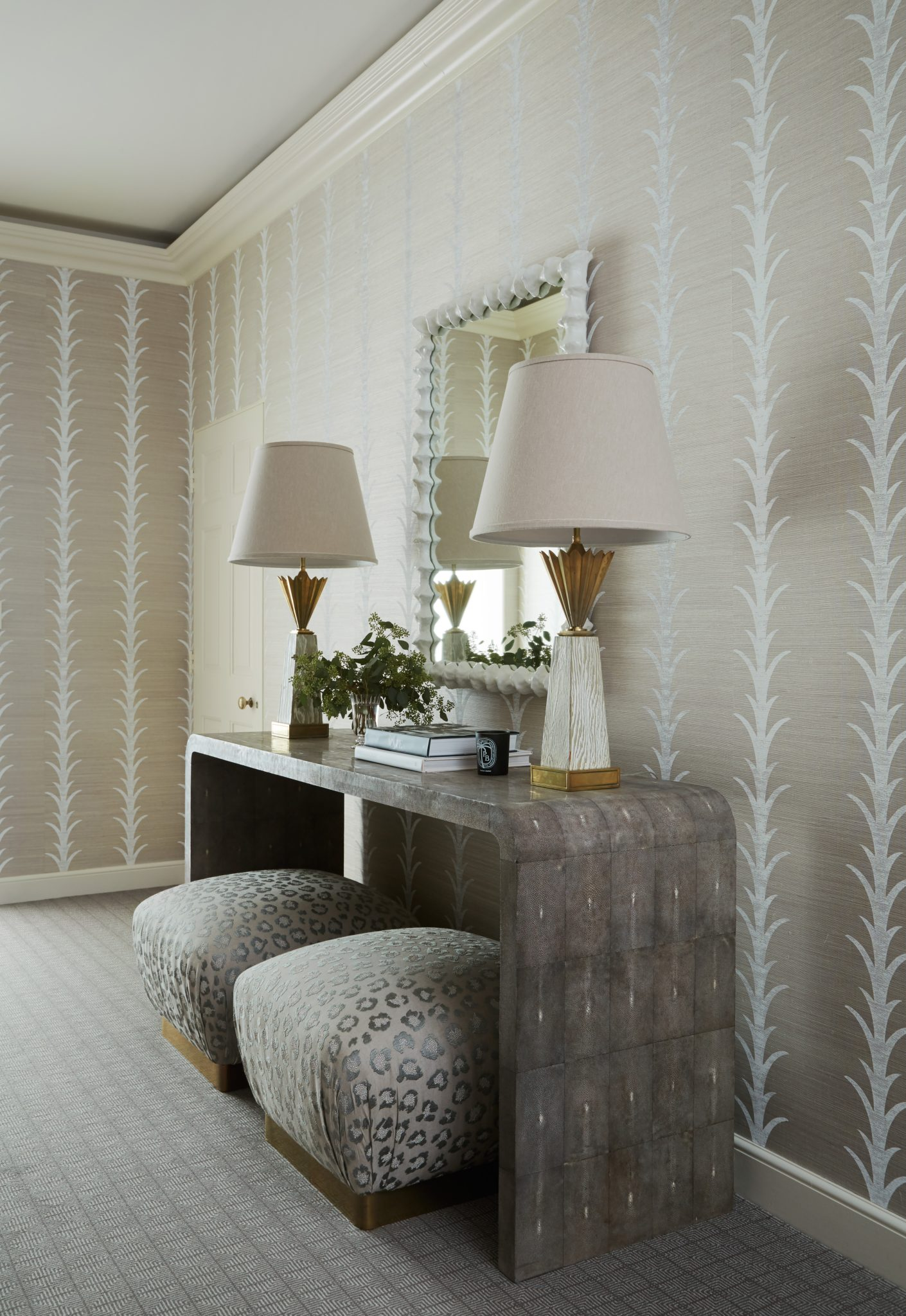 Lake Forest hallway with trellis painted grasscloth wallpaper, snakeskin table and vintage lamps. The brass footed ottomans are upholstered in an embroidered leopard print pattern. By Caitlin Moran Interiors