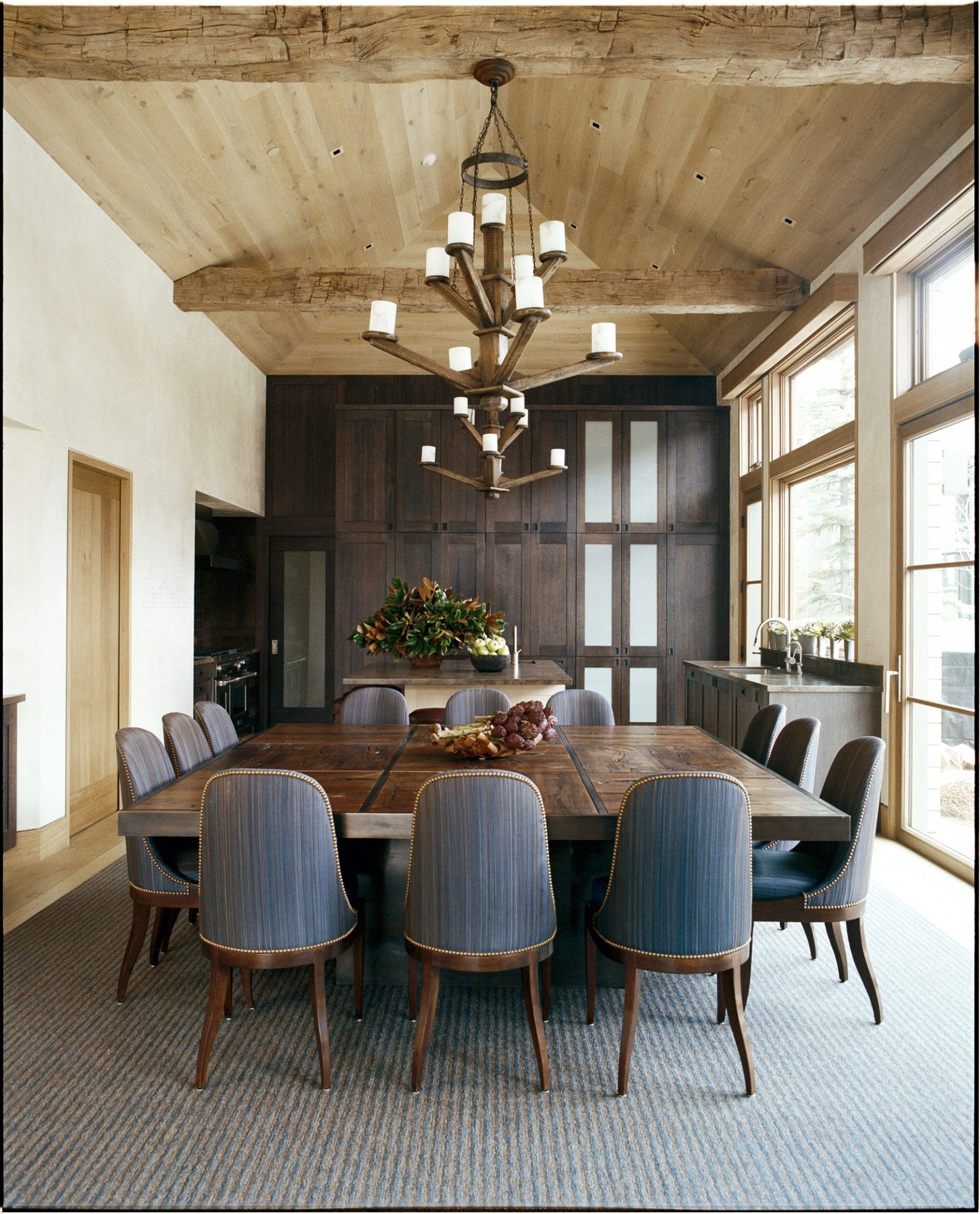 Bright dining room with rustic beams, shades of wood by Stephen Sills Associates