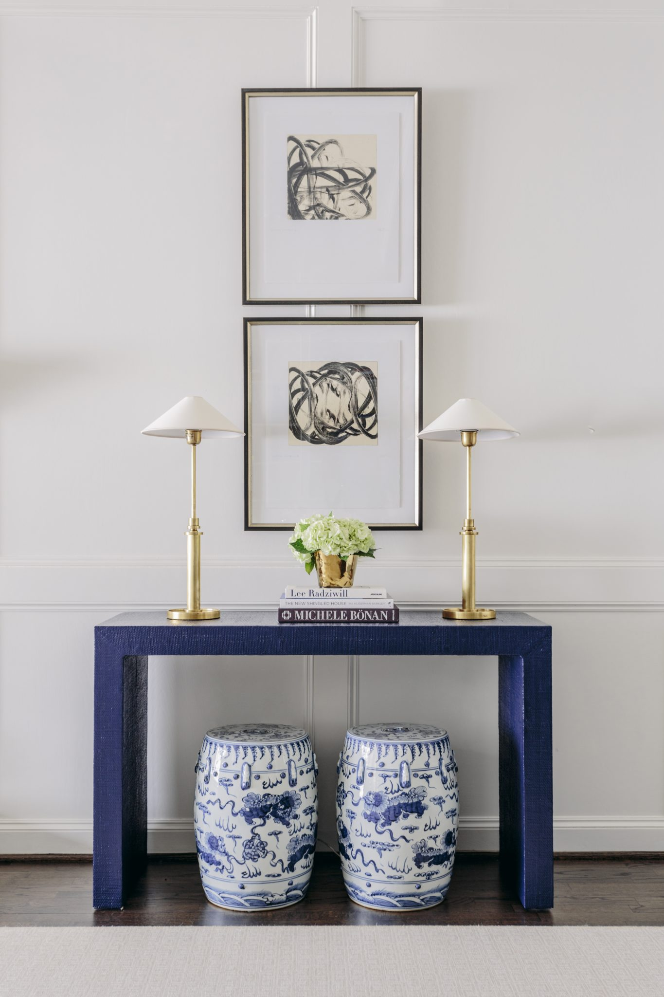 Houston living room with navy Parsons table, brass lamps, abstract art, and blue andwhite stools. By Paloma Contreras Design