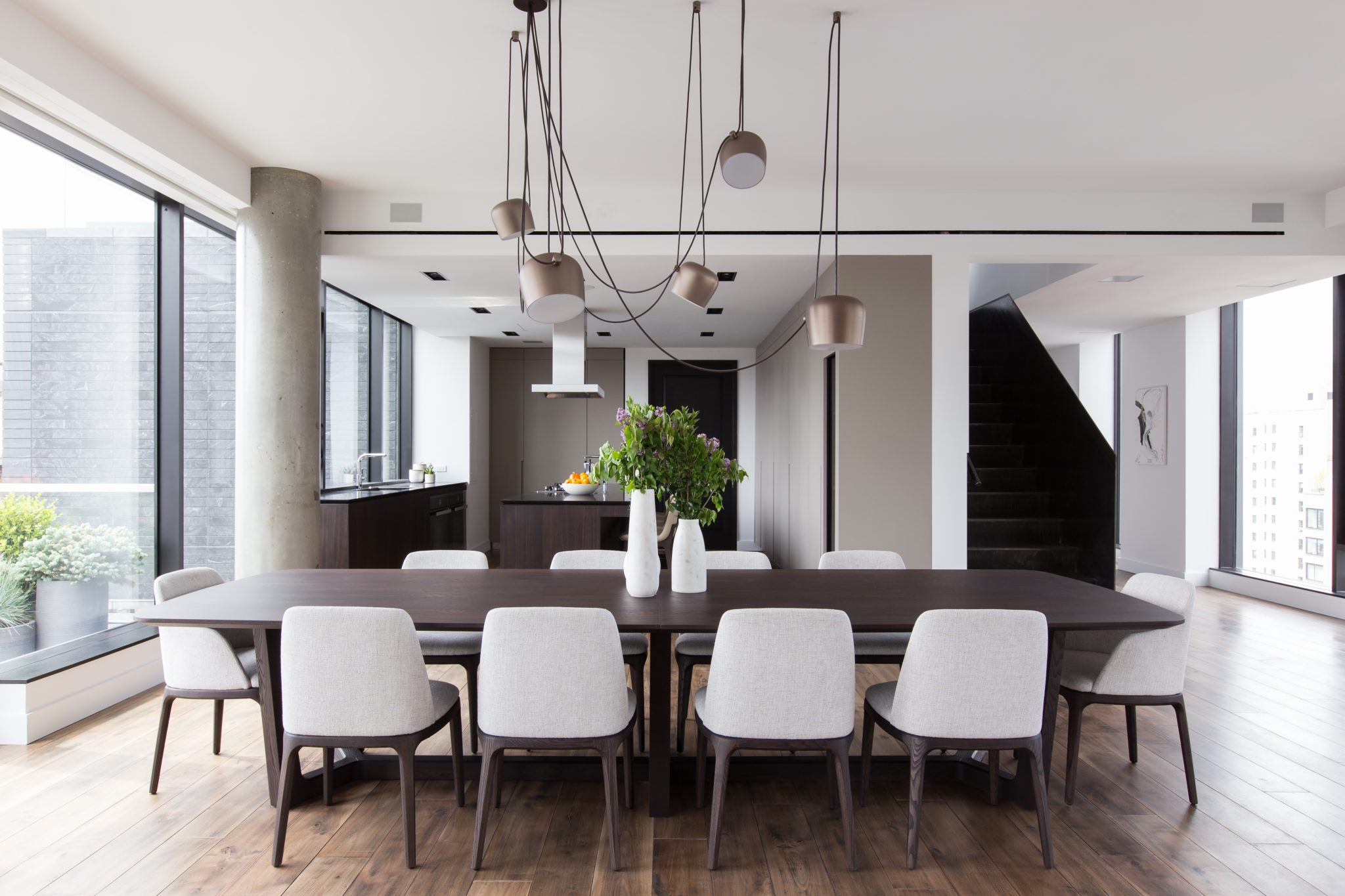 Dining room with custom table and modern chandelier by B Interior LLC