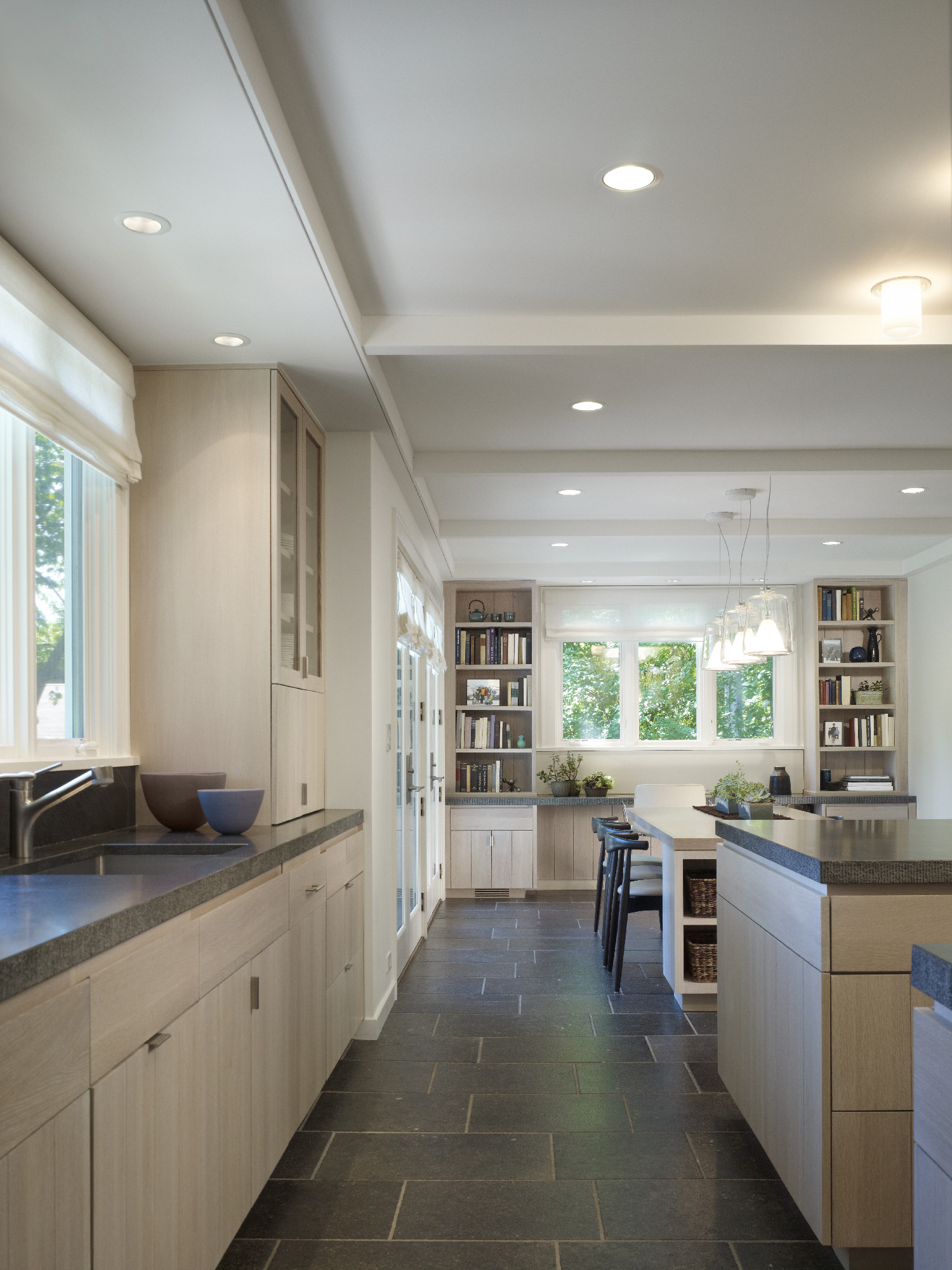 Farm house renovation - Tongue and Groove cabinets with dark limestone floors by Robbins Architecture