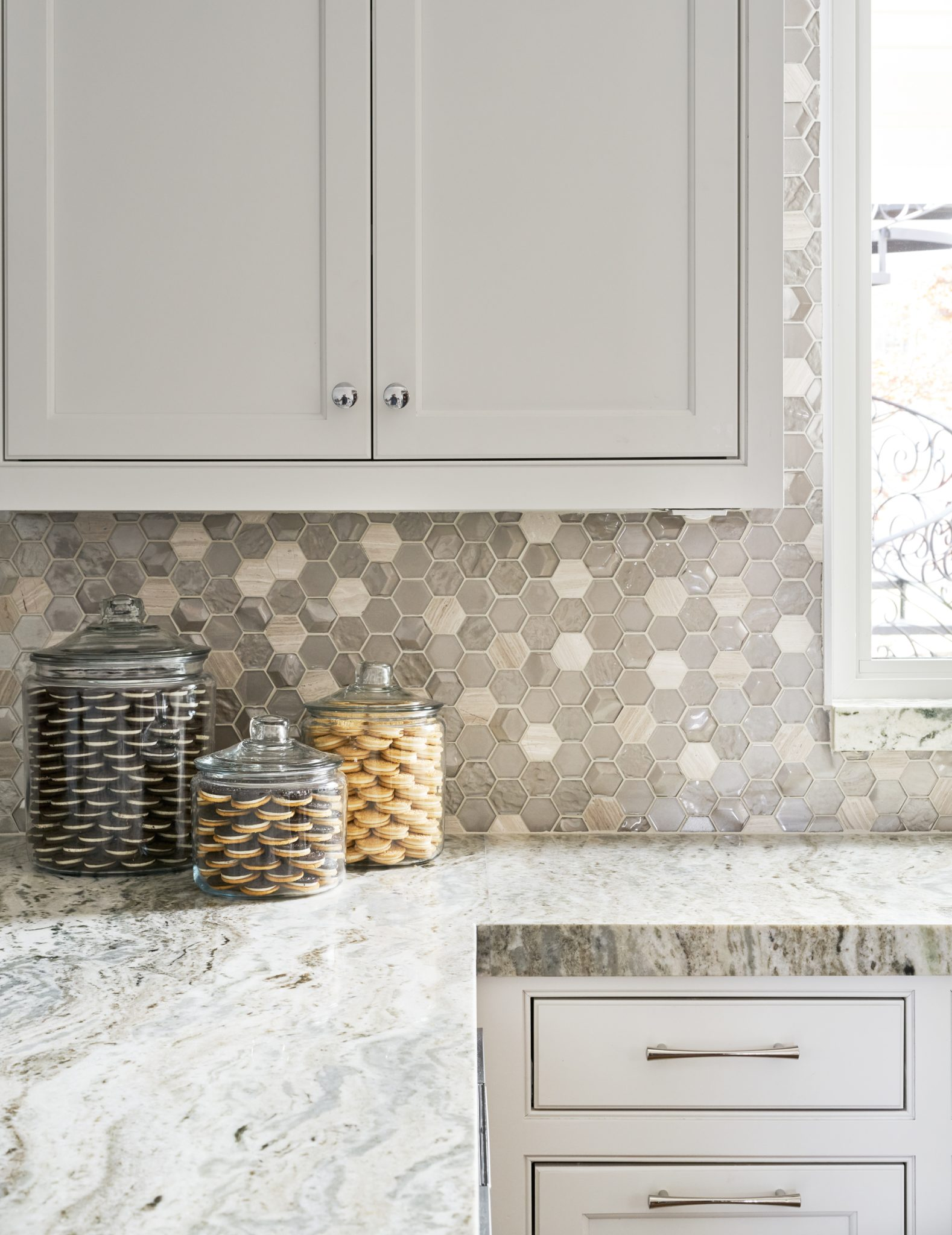 This kitchen features waterfall edges and a fabulous mosaic tile backsplash. by Wesley-Wayne Interiors