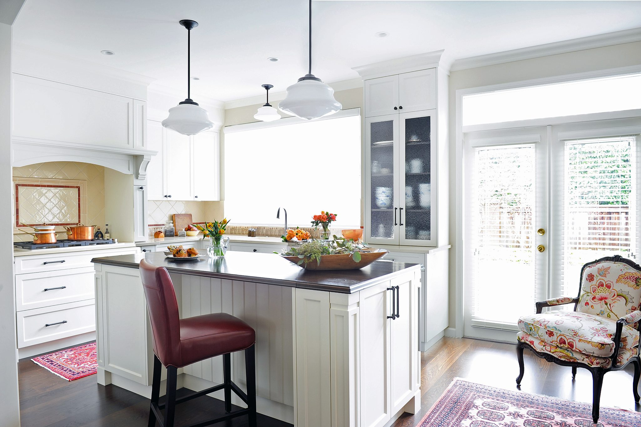 Warm Hampton Place townhouse kitchen with wood-topped island by Enviable Designs