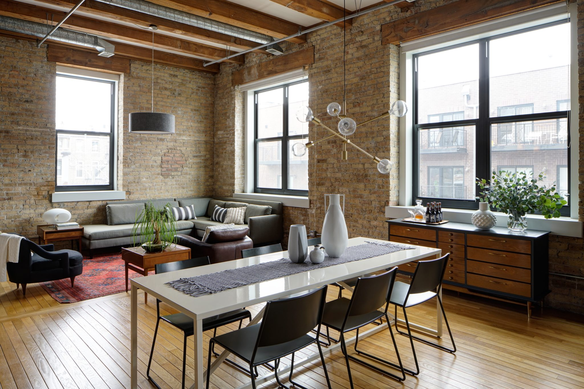 Chicago renovated loft, open concept dining and living room, and exposed brick by Maren Baker Design