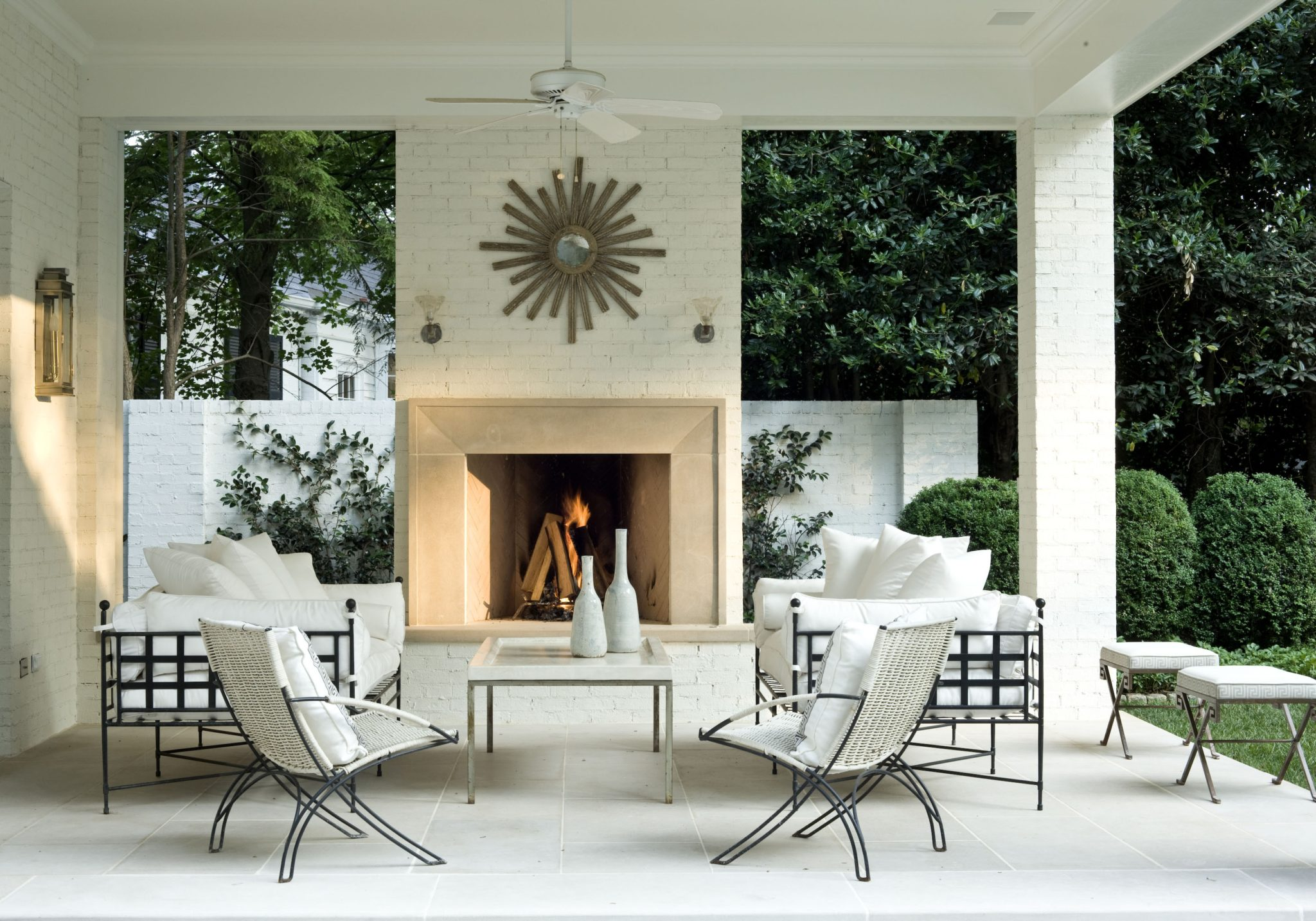 A patio with an outdoor fireplace anddesigns by Suzanne Kasler Interiors