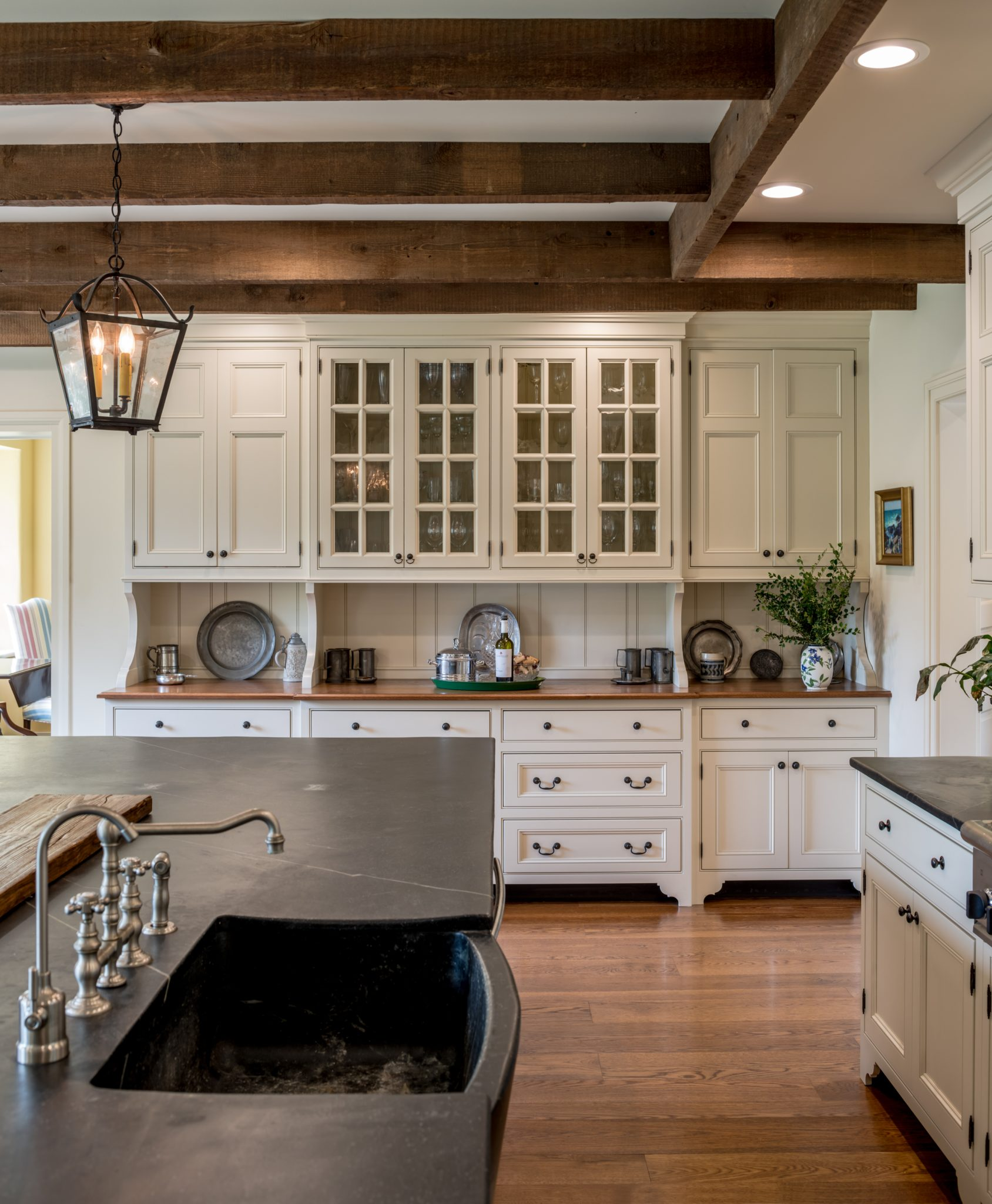 Open farmhouse kitchen with wood beams, display cabinetry & large central island by Period Architecture