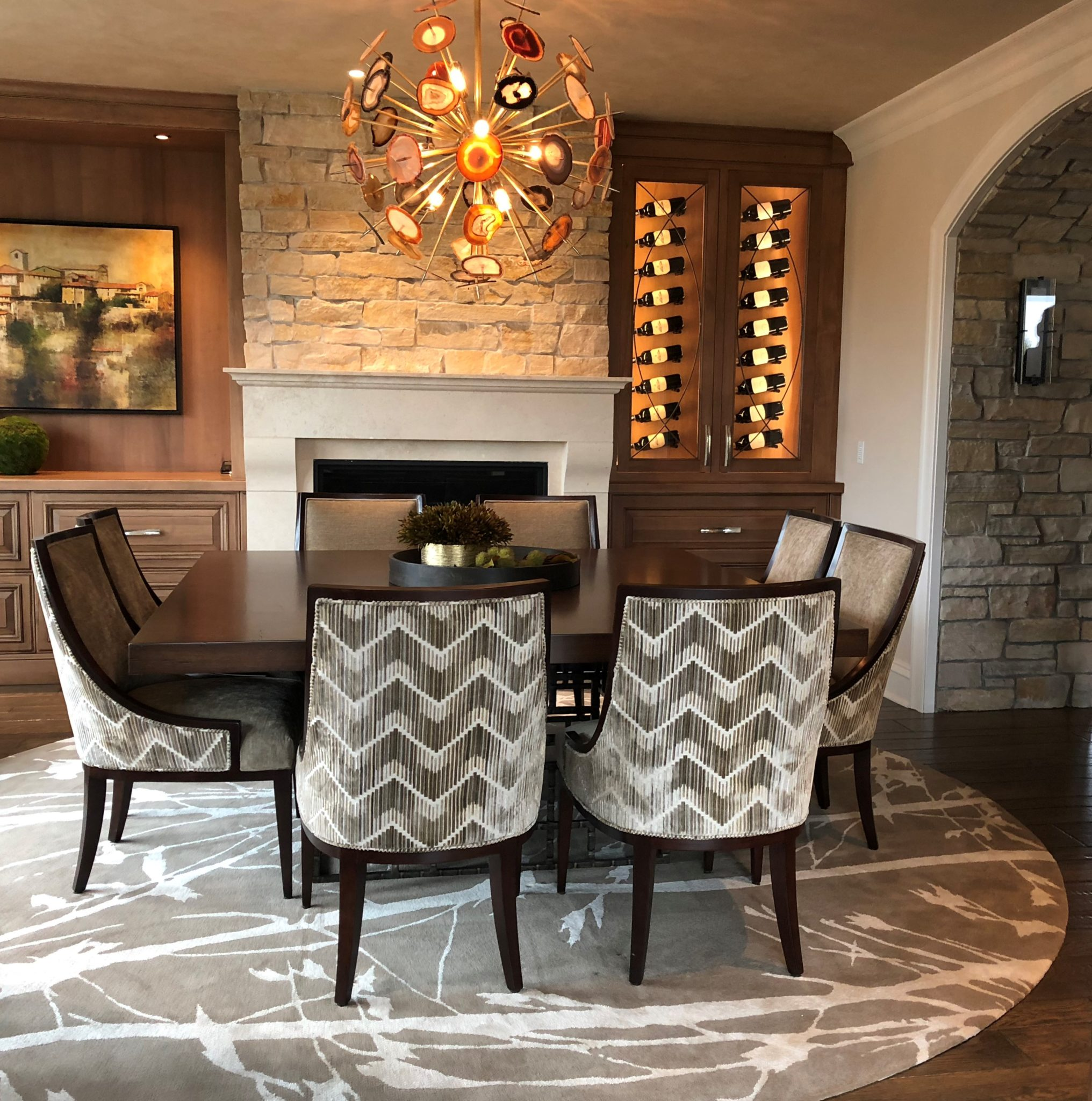 Square dining table with chevron chairs, agate chandelier, custom abstract rug by Interior Enhancement Group