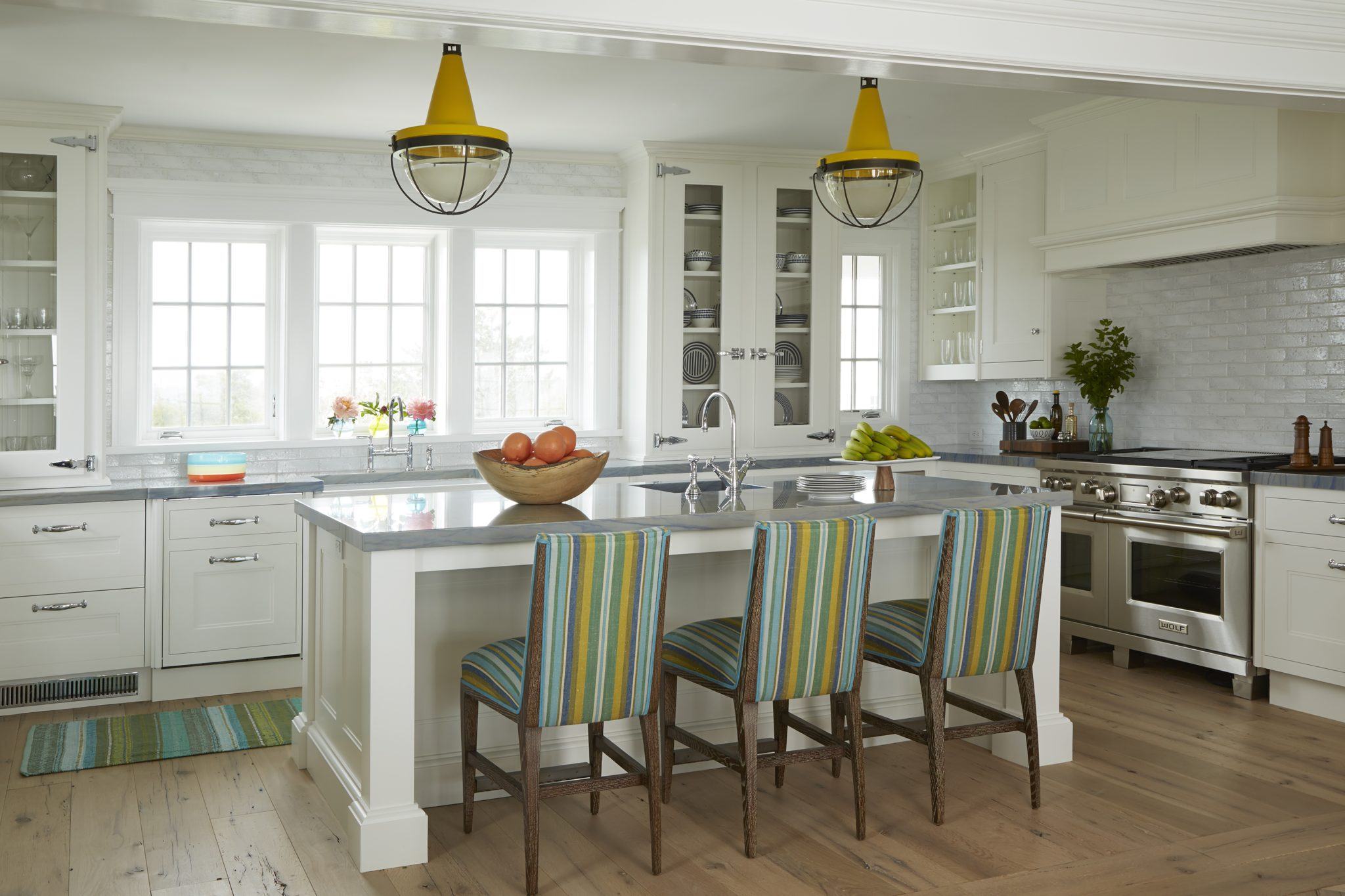 Hanging marigold pendants pick up accent colors in the barstools' fabric. by Scott Sanders