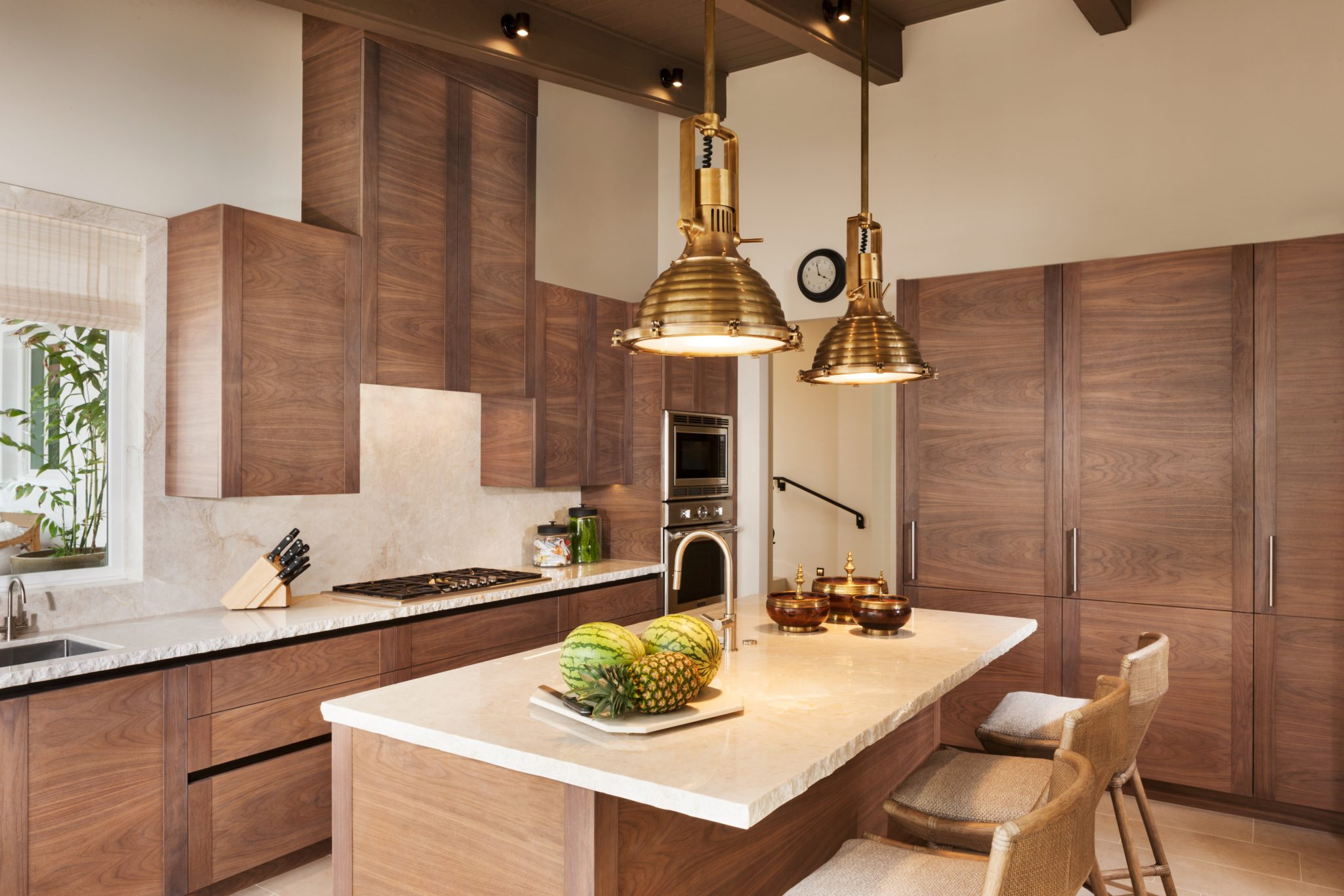 Walnut veneer with brass pendant island lighting. Kitchen counter stools. by Cooper Pacific Kitchens